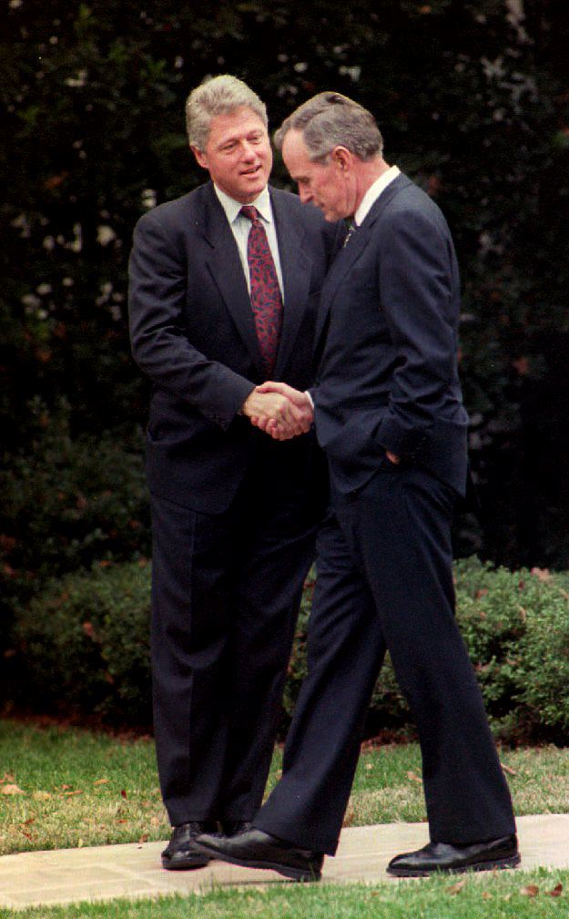 WASHINGTON, : U.S. President George Bush (R) shakes hands with President-elect Bill Clinton 18 November 1992 as Clinton leaves the White House after a meeting about the transition between administrations. This is Clinton's first visit to Washington since winning the 03 November presidential election. (Photo credit should read LUKE FRAZZA/AFP/Getty Images)