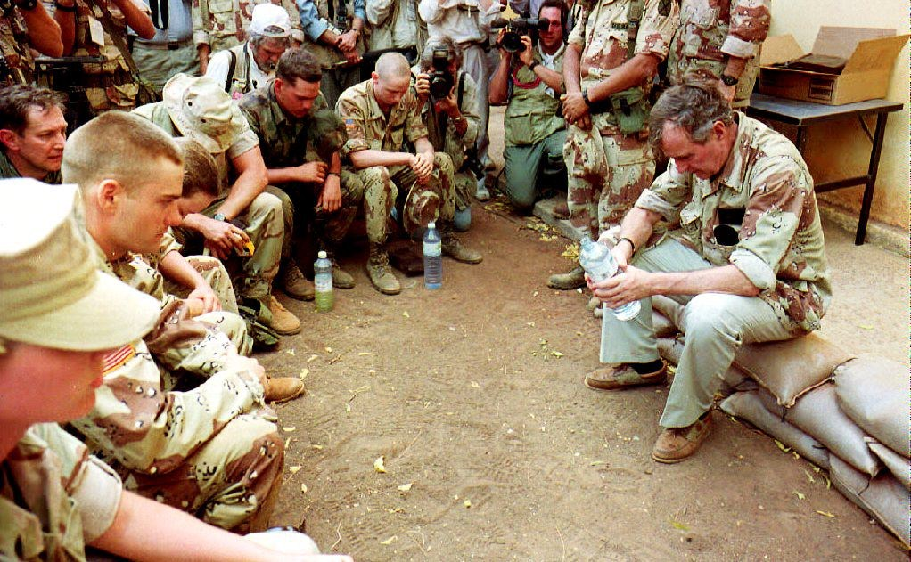 U.S. President George Bush prays 01 January 1993 with Marines before having a military lunch at the Baledogle airbase. Bush is in Somalia visiting with the troops involved in Operation Restore Hope. (Photo credit should read DAVID AKE/AFP/Getty Images)