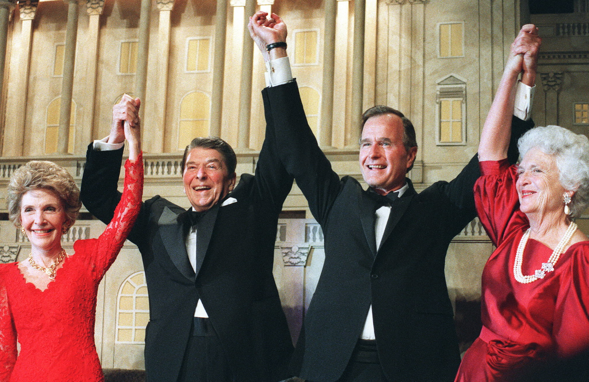 WASHINGTON, DC - NOVEMBER 5: US President Ronald Reagan (l) raises his arms in the air with presidential hopeful George Bush (2nd-r) after President Reagan announced endorsement for Bush as the next president of the United States in Washington DC, 05 November 1988. At left, First Lady Nancy Reagan, at right, Barbara Bush. (Photo credit should read MIKE SARGENT/AFP/Getty Images)