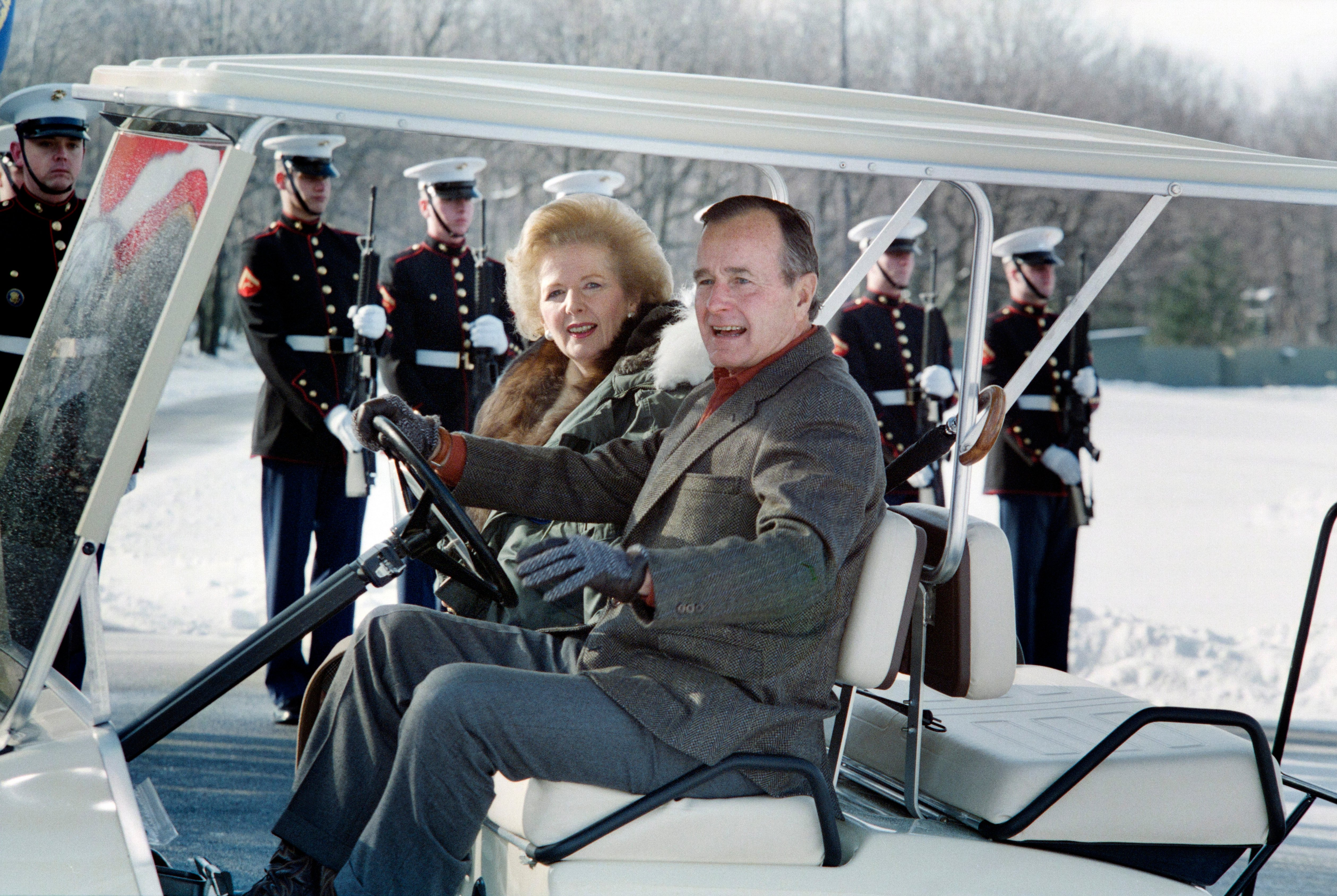 US President George Bush (R) and British Prime Minister Margaret Thatcher (L) drive away in a golf cart on November 24, 1989 from the helicopter landing zone at Camp David. Thatcher is scheduled to have a four hour meeting with the President. (Photo credit should read LUKE FRAZZA/AFP/Getty Images)