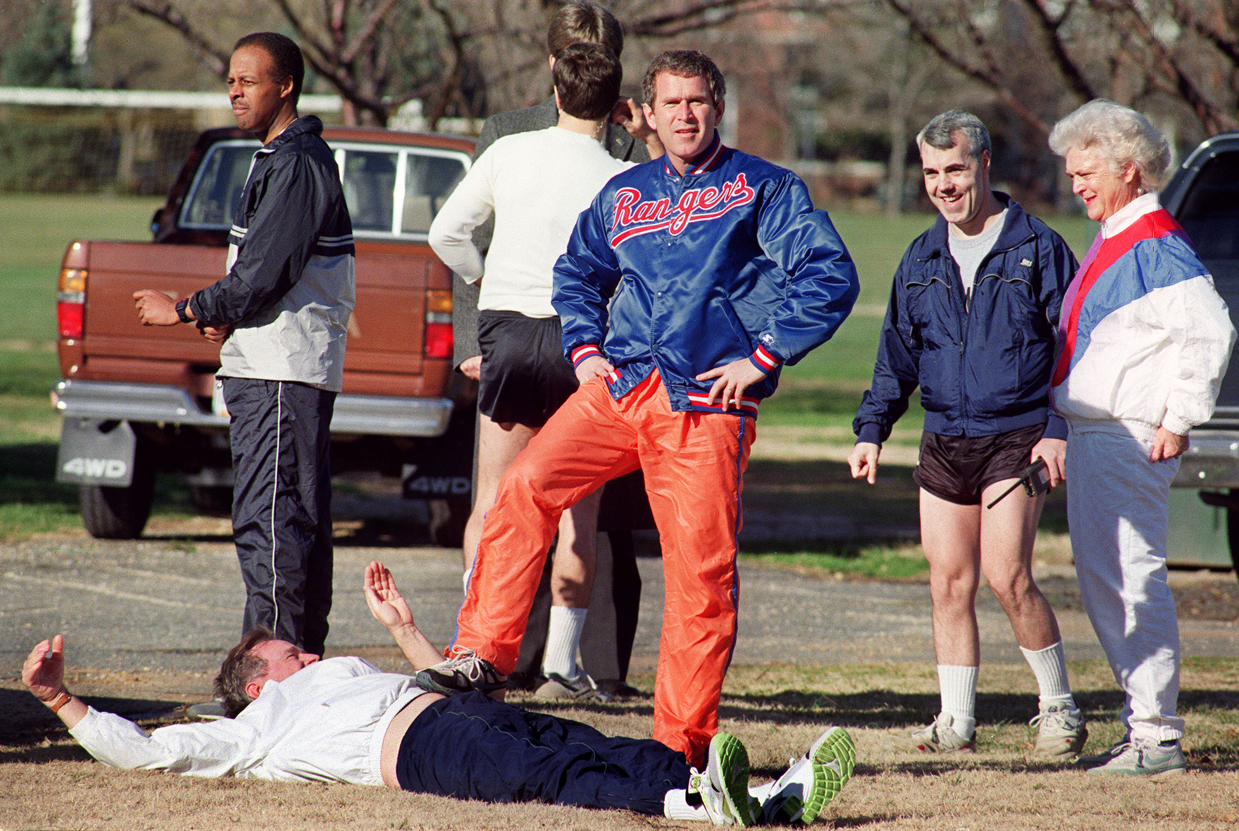 WASHINGTON, DC - JANUARY27: George W. Bush, son of the US President George Bush, playfully steps upon his father 27 January 1990 while he warms up for a run at Fort McNaire Army base while his mother Barbara (R) and US Secret Service agents look on. AFP PHOTO KEVIN LARKIN (Photo credit should read KEVIN LARKIN/AFP/Getty Images)