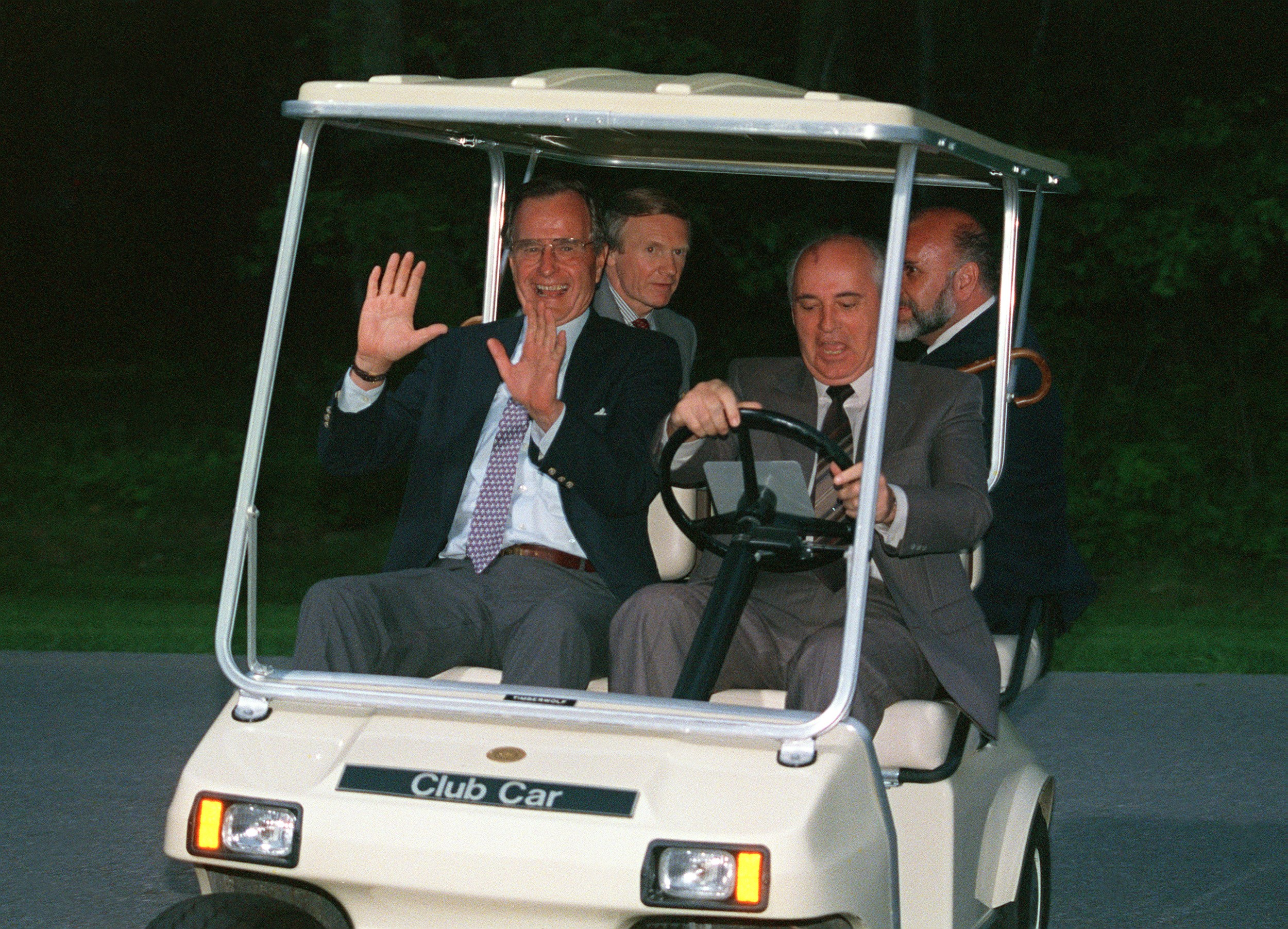 Soviet President Mikhail Gorbachev (R) takes US President George Bush (L) for a ride in President Bush's golf cart 02 June 1990. The two leaders were on their way back to their helicopter for the flight back to Washington after a day at the presidential retreat in Camp David. (Photo credit should read JEROME DELAY/AFP/Getty Images)