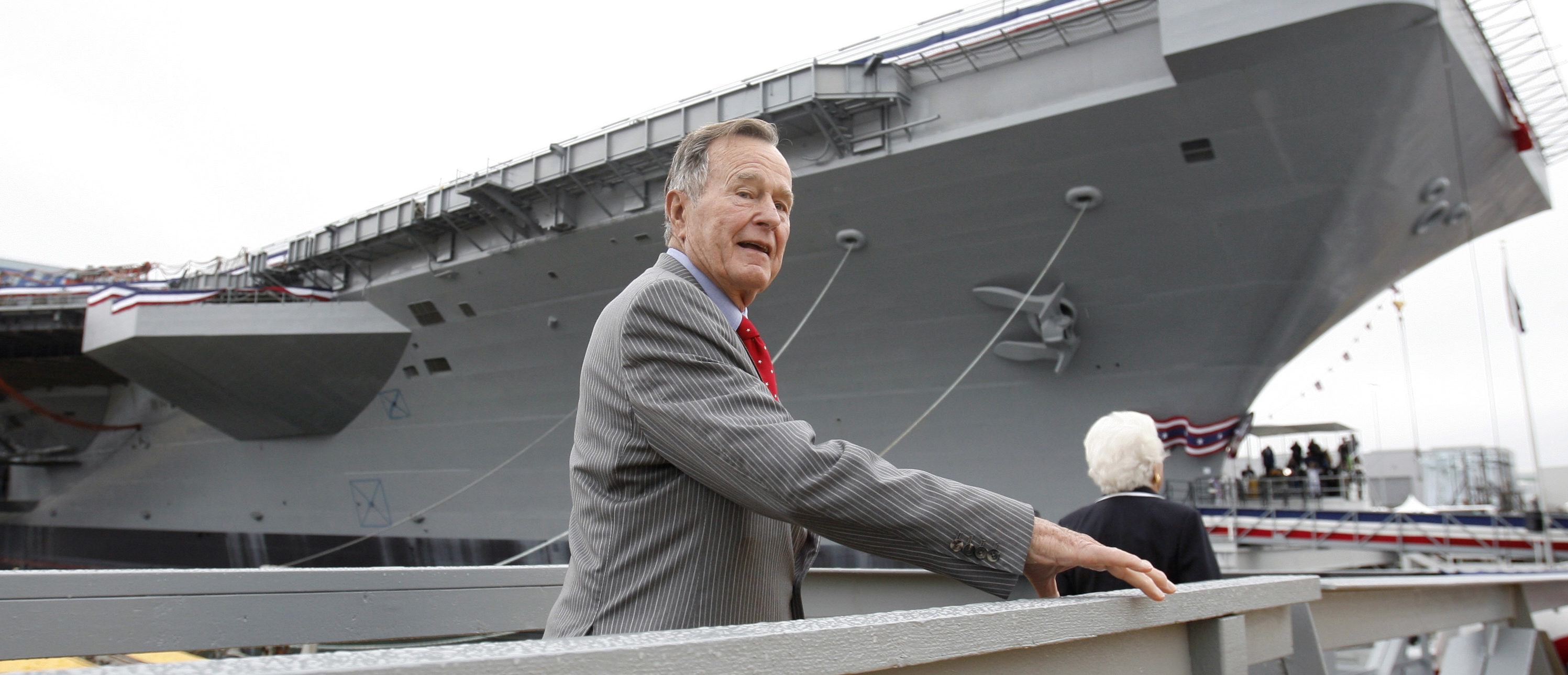 Former president George H. W. Bush walks the gangway as he arrives for the christening ceremony of the USS George H.W. Bush at Northrop-Grumman's shipyard in Newport News, Virginia, October 7, 2006. The Navy's Nimitz-class aircraft carrier is scheduled to enter service in late 2008. REUTERS/Kevin Lamarque