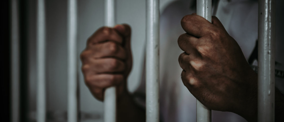 A man is behind bars. Shutterstock image via user kittirate roekburiA man is behind bars. Shutterstock image via user kittirat roekburi