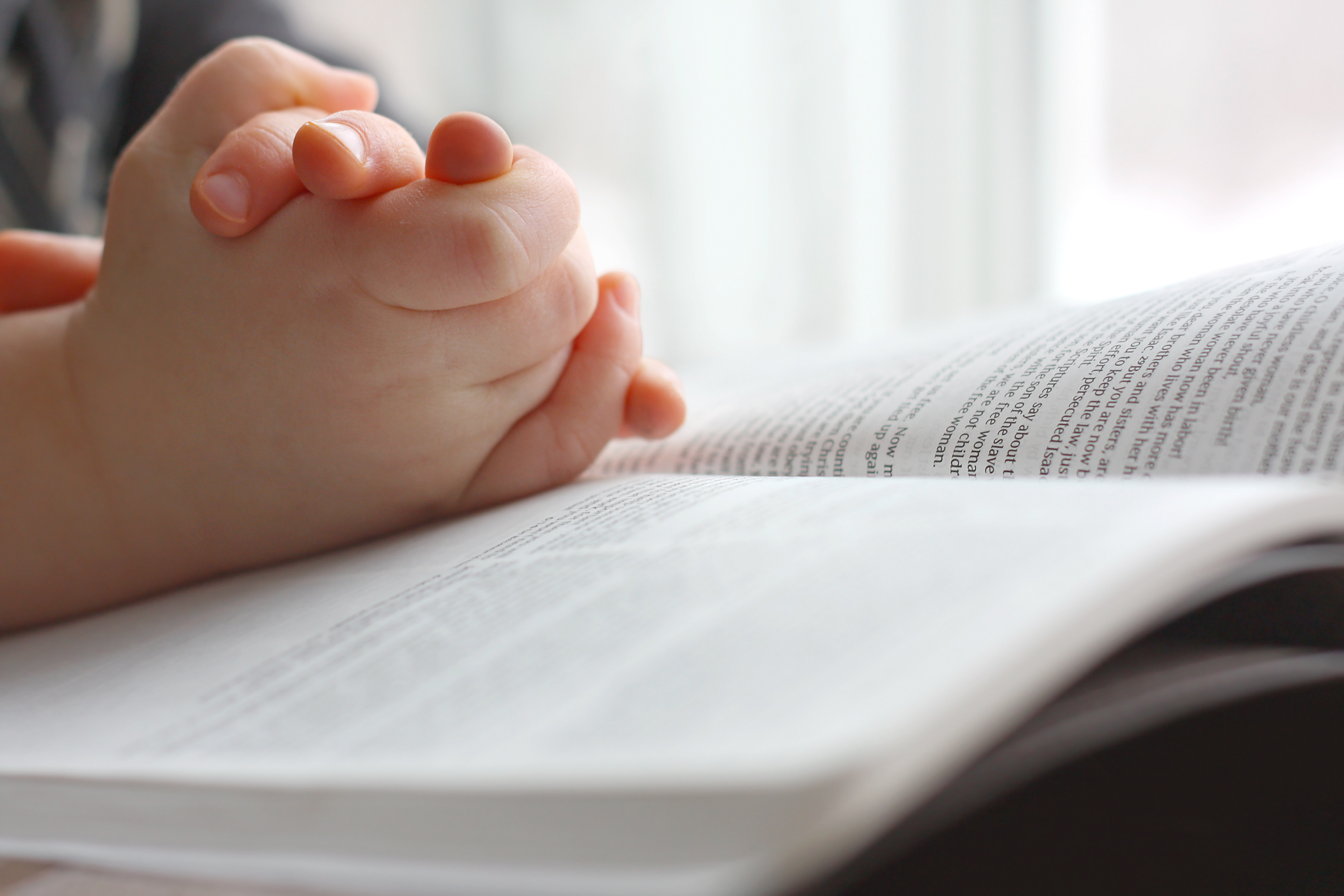A student prays over the Bible. Shutterstock image via user Christin Lola