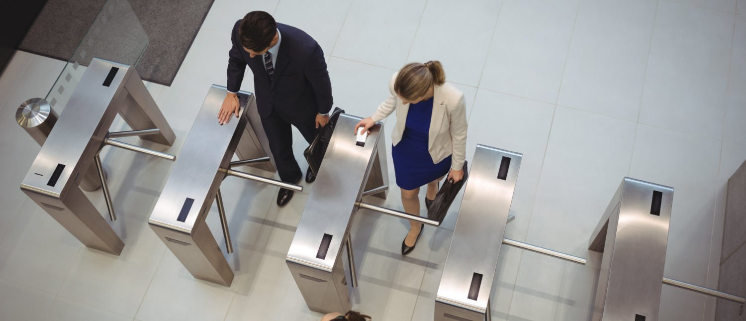 Top view of business executives passing through turnstile gates. [Shutterstock - wavebreakmedia]
