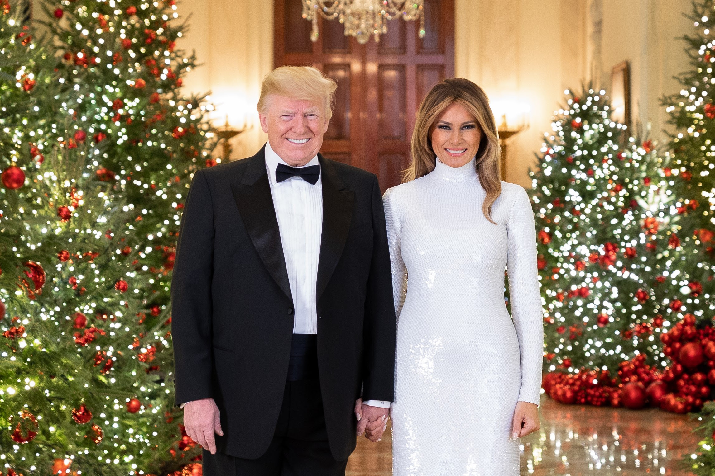 President Donald J. Trump and First Lady Melania Trump are seen in their Official Christmas Portrait on Saturday, December 15, 2018, in the Cross Hall of the White House in Washington, D.C. (Official White House Photo by Andrea Hanks)