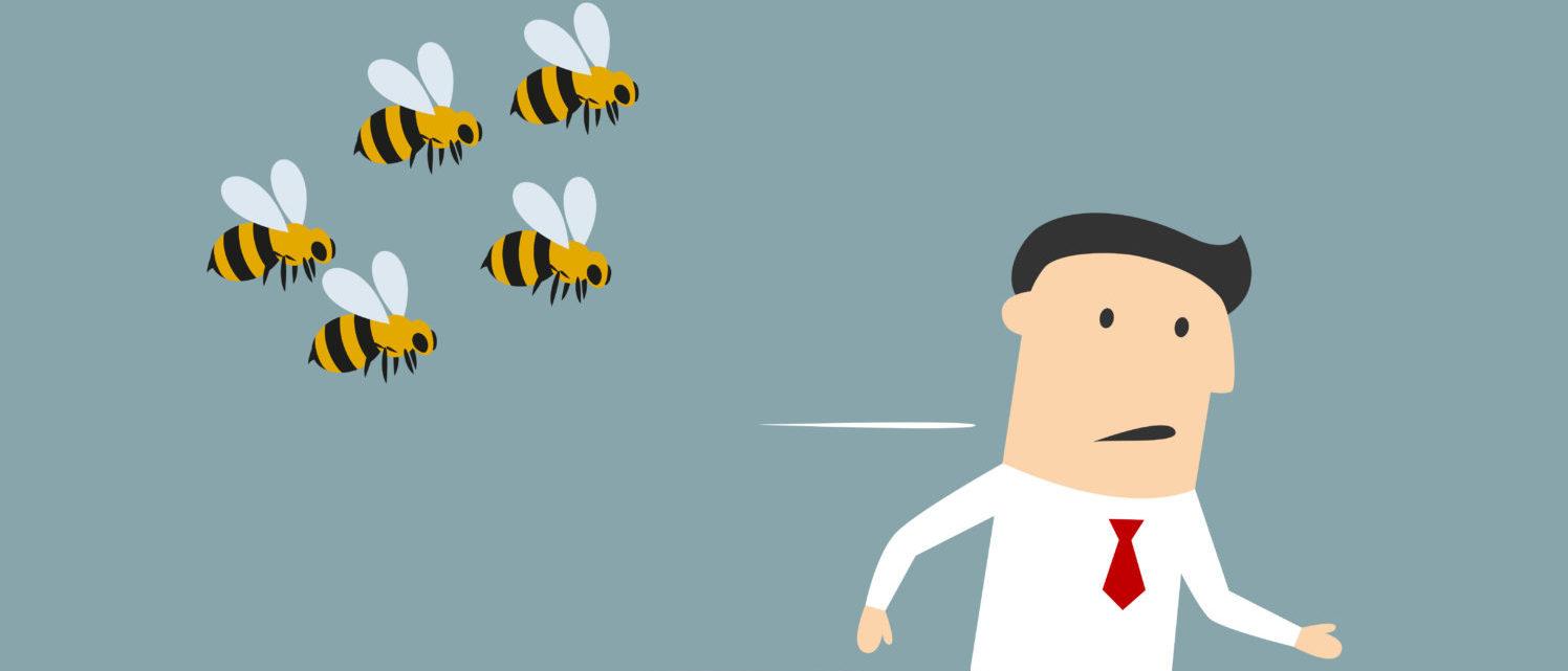 A man runs from bees. By Shutterstock.