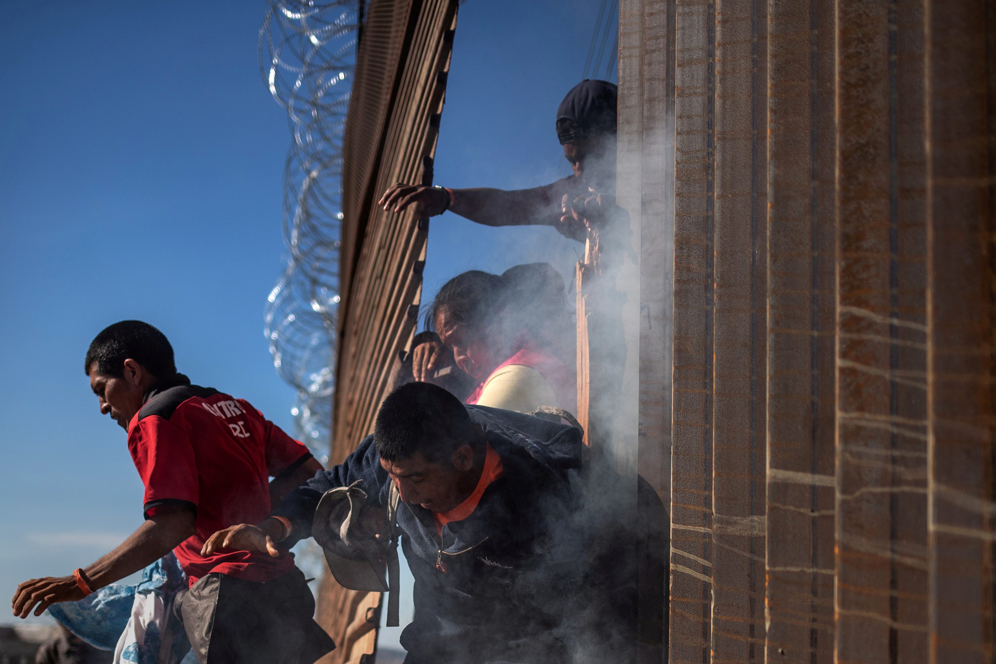 Migrants are hit by tear gas by U.S. Customs and Border Protection after attempting to illegally cross the border wall into the U.S. in Tijuana, Mexico