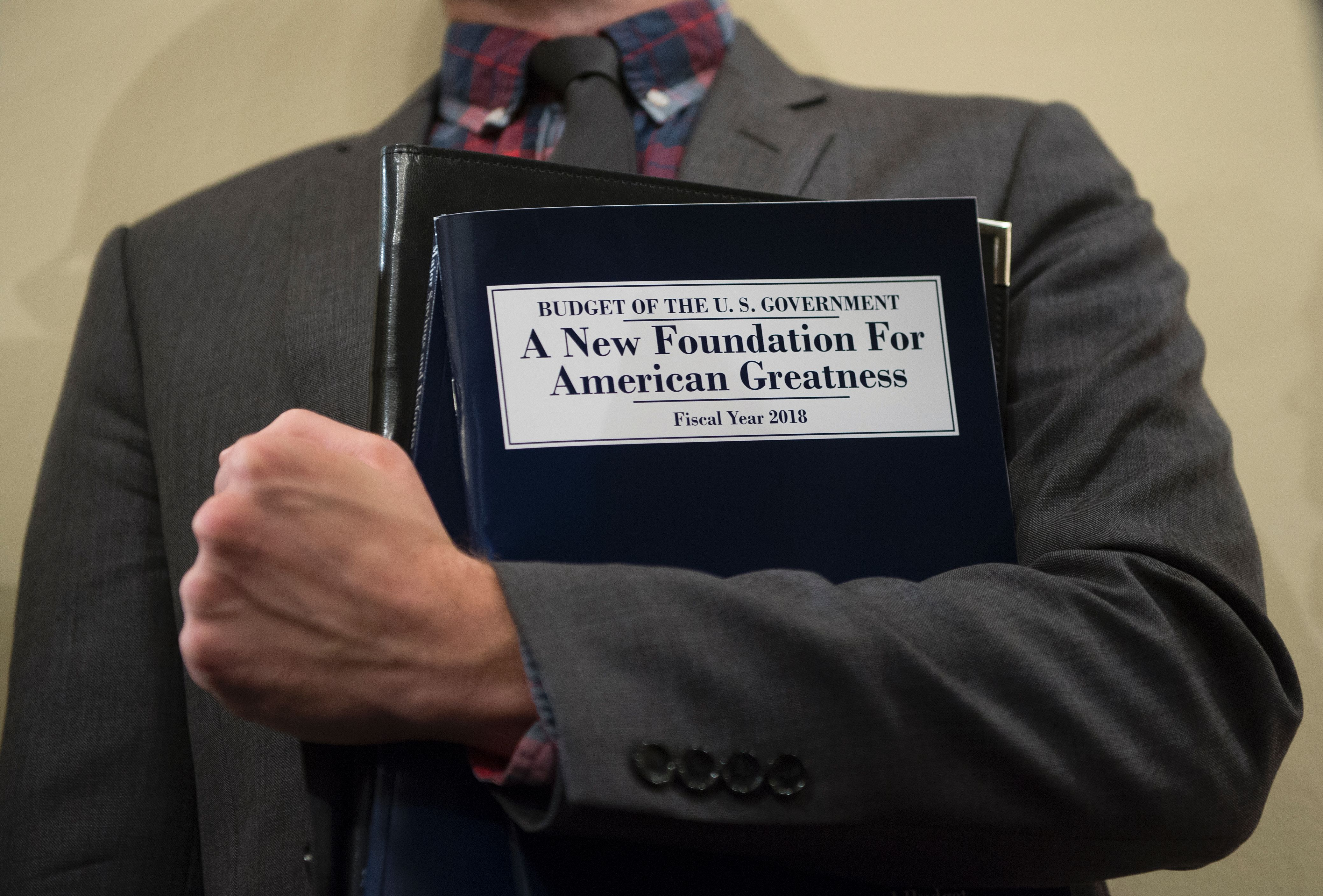 A man holds a copy of the FY2018 budget as Director of the OMB testifies at a House Budget Committee (Andrew Caballero-Reynolds/AFP/Getty Images)