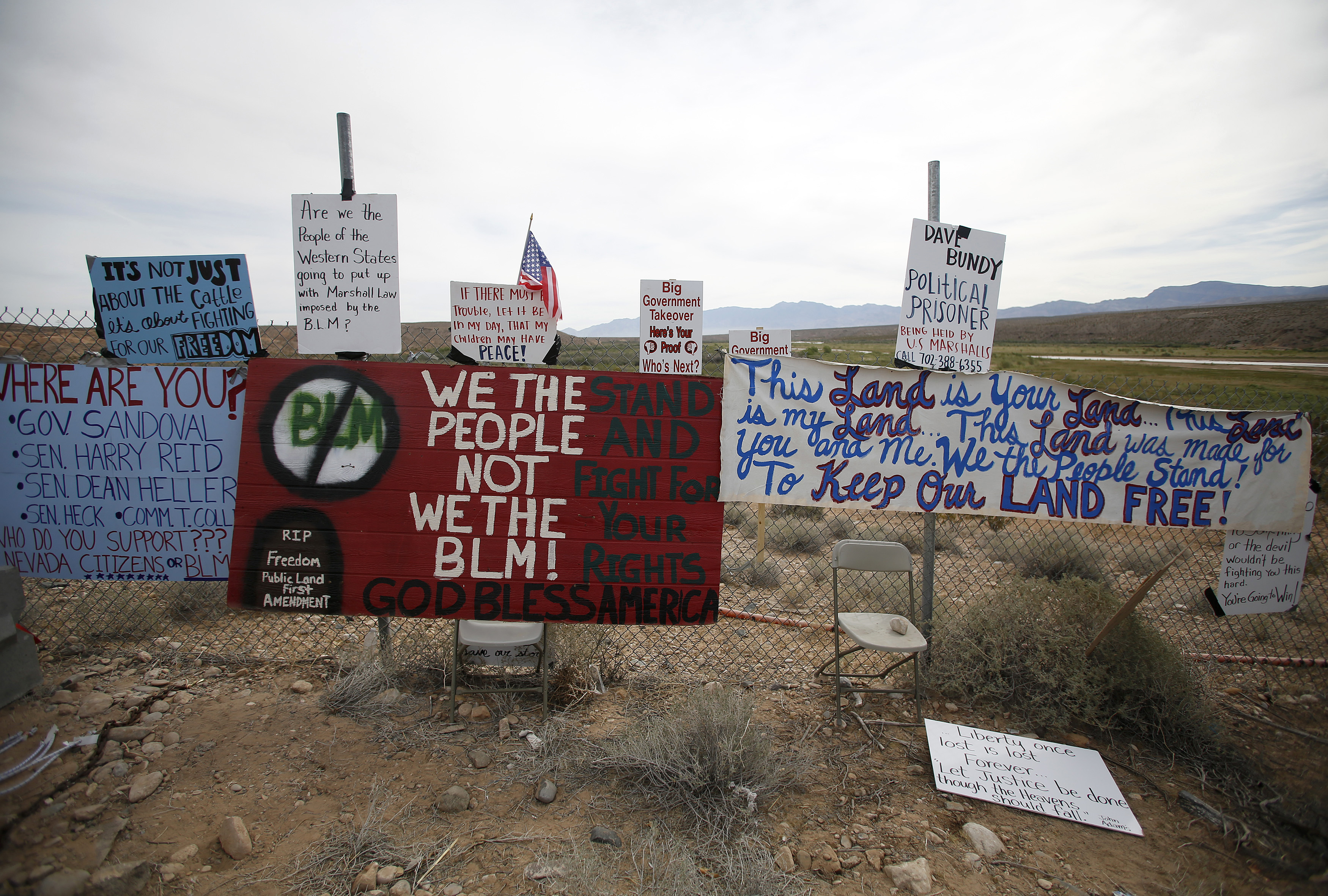Protest signs are seen on a fence in Bunkerville, Nevada, April 11, 2014. REUTERS/Jim Urquhart