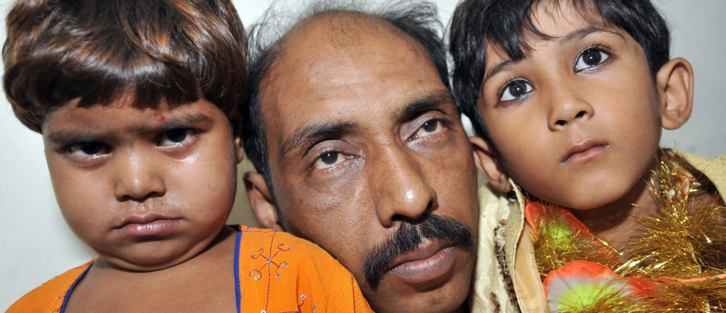 Muhmad Islamil (C), father of underage groom hold his ten year old son Muhmad Wasim (R) and his three year old bride Nisha Nasir (L) in police custody in Karachi on October 31, 2008. Police arrested the children's fathers and a marriage registrar in the Nazimabad area of the southern city of Karachi, amid claims that a four-year-old girl and seven-year-old boy were being wedded unlawfully. (RIZWAN TABASSUM/AFP/Getty Images)