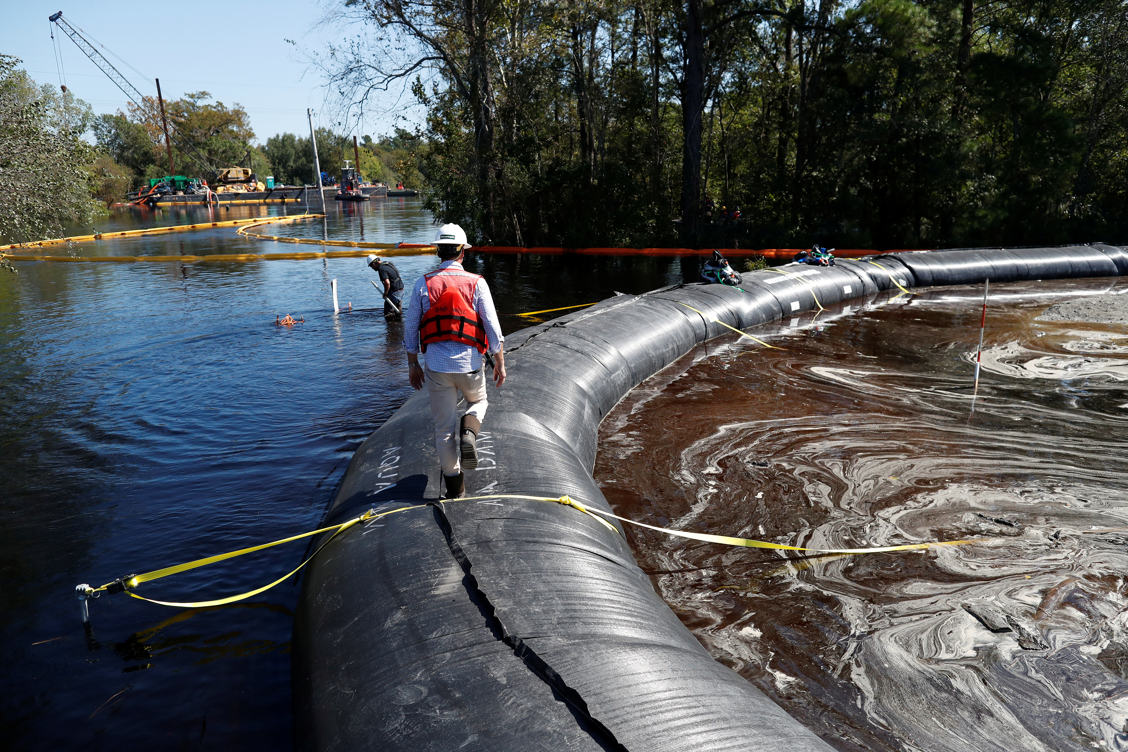 Santee Cooper workers check the water levels around a 6000 foot long Aqua Dam built to keep sediment from a coal ash retention pond from going into the flooded Waccamaw River in the aftermath of Hurricane Florence in Conway