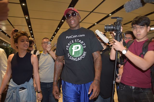 "Retired American professional basketball player Dennis Rodman speaks to the press as he arrives at Changi International airport ahead of US-North Korea summit in Singapore on June 11, 2018. - North Korea's Kim Jong Un and US President Donald Trump meet on June 12 for an unprecedented summit in an attempt to address the last festering legacy of the Cold War, with the US President calling it a ""one time shot"" at peace. (Photo credit: ADEK BERRY/AFP/Getty Images)"