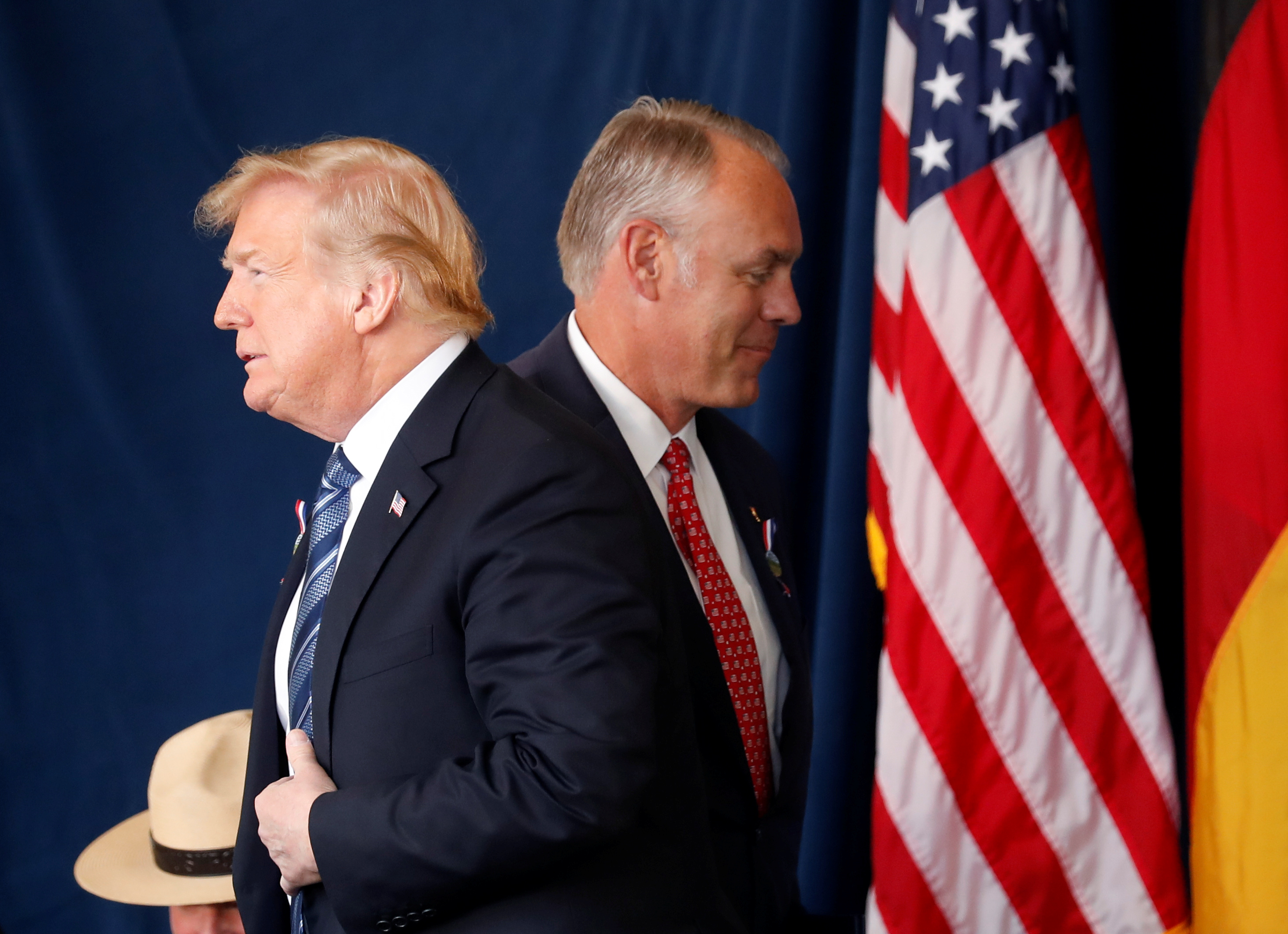 U.S. President Donald Trump walks past Interior Secretary Ryan Zinke as he stands to address the 17th annual September 11 observance at the Flight 93 National Memorial near Shanksville, Pennsylvania, U.S., September 11, 2018. REUTERS/Kevin Lamarque