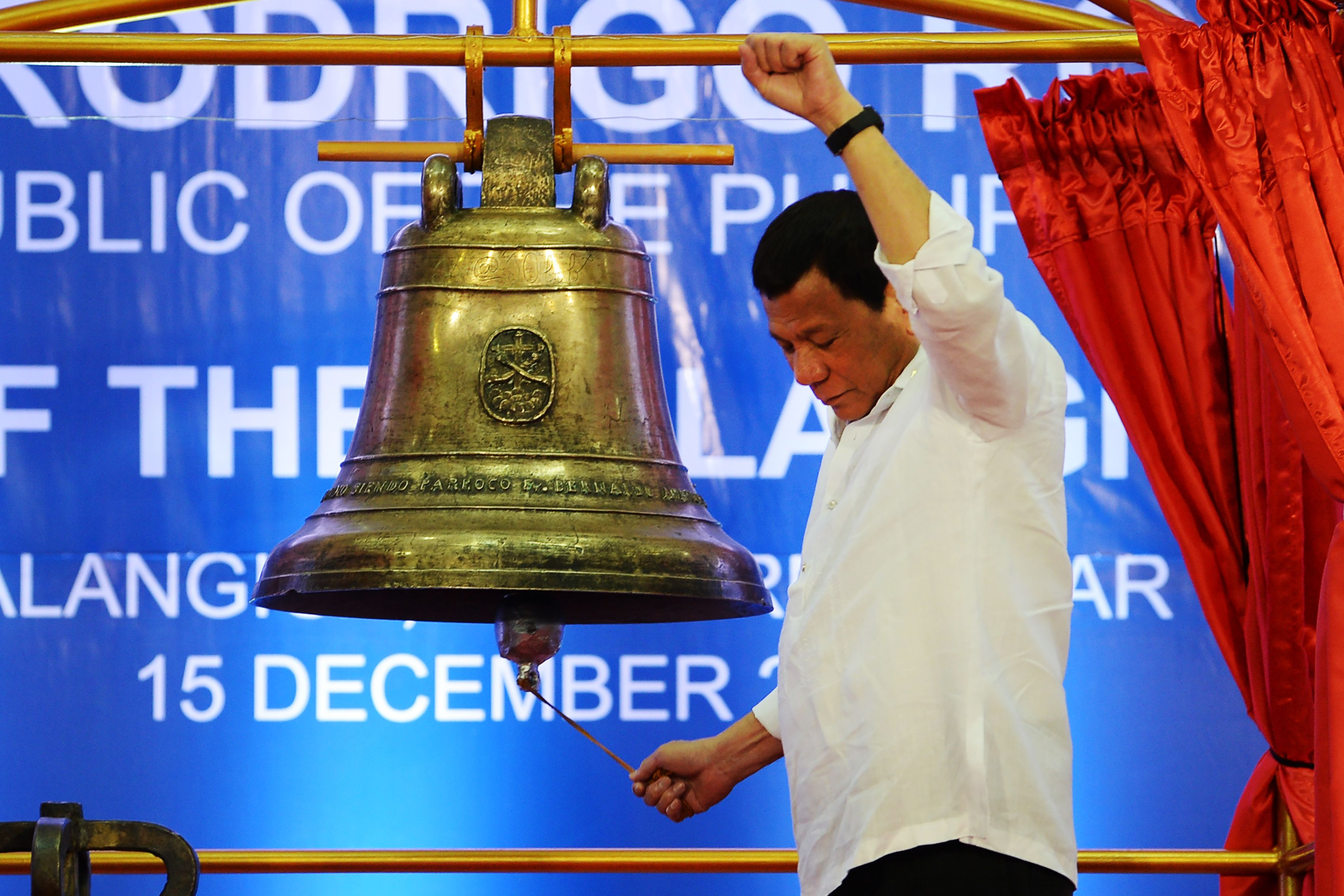 Philippine President Rodrigo Duterte raises a clenched fist as he rings one of the three Balangiga church bells during a ceremony in Balangiga in Eastern Samar province on December 15, 2018. (TED ALJIBE/AFP/Getty Images)