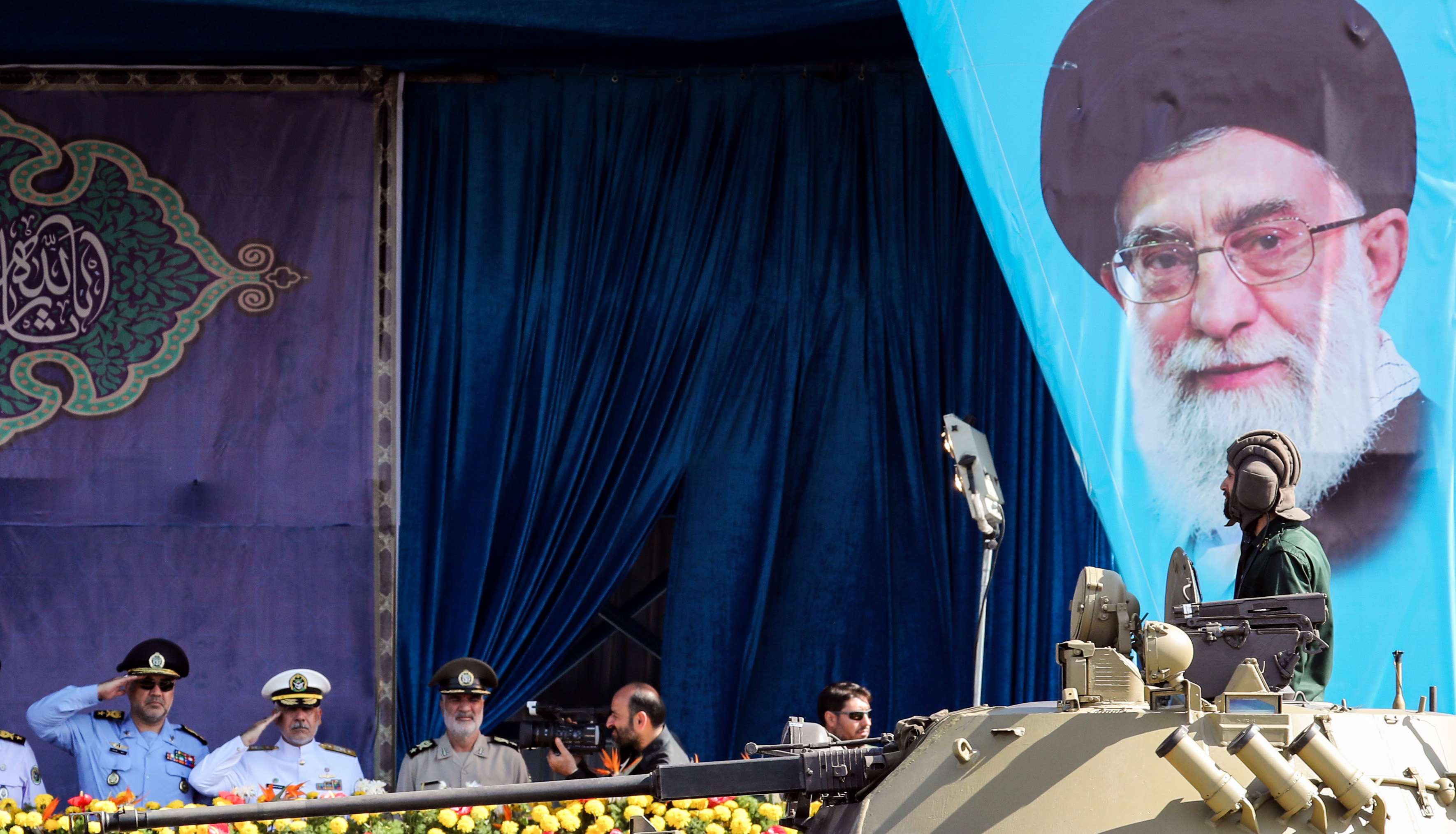 This picture taken on September 22, 2018 shows an Iranian soldier seated in the turret of a tank passing by a large poster of the country's Supreme Leader Ayatollah Ali Khamenei and a stand where the president is seated, during the annual military parade marking the anniversary of the outbreak of the devastating 1980-1988 war with Saddam Hussein's Iraq, in the capital Tehran. (STR/AFP/Getty Images)