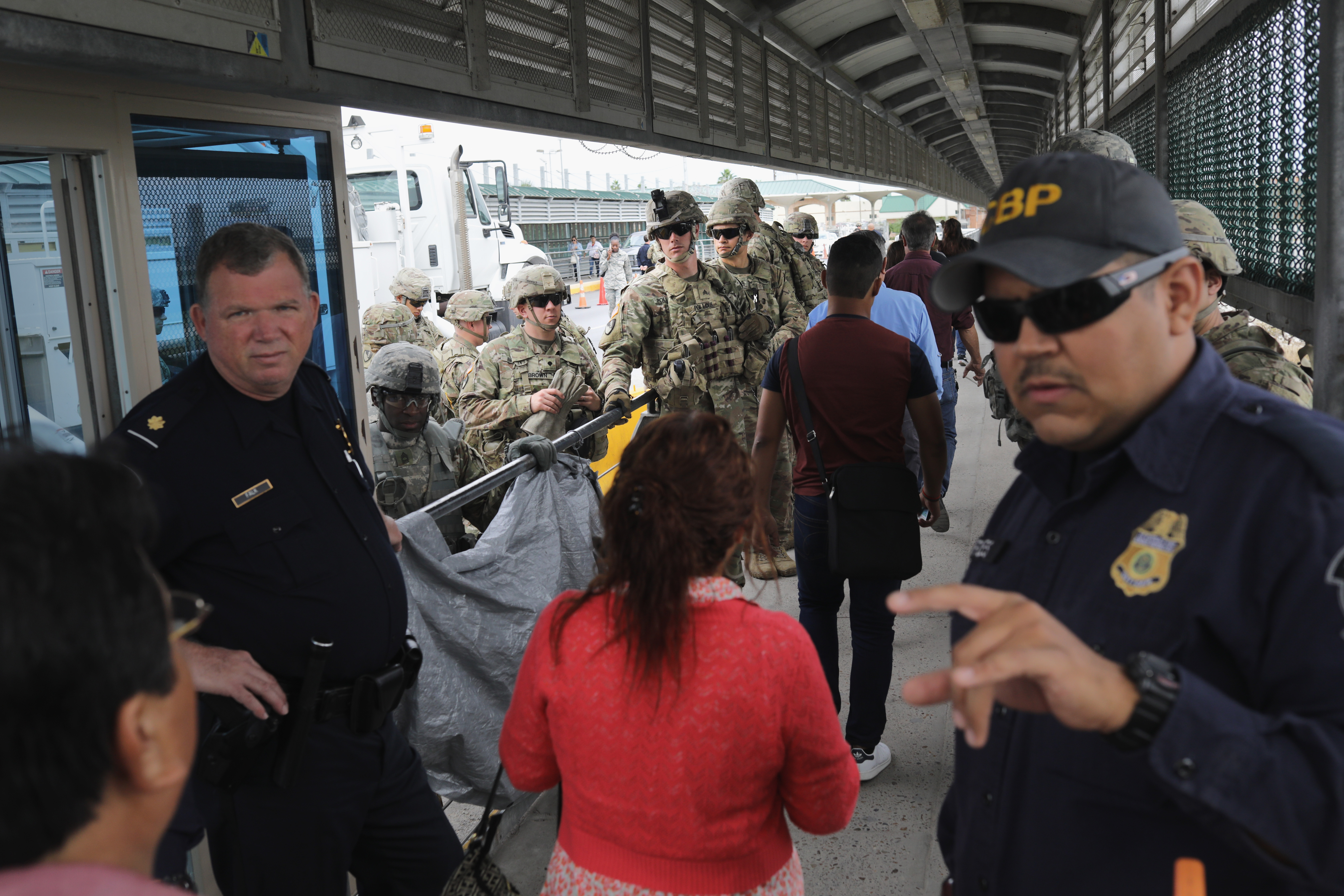U.S. Customs and Border Protection officers and U.S. Army troops allow people to pass over the international bridge with Mexico to an immigration checkpoint on November 2, 2018 in Hidalgo, Texas. (Photo by John Moore/Getty Images)