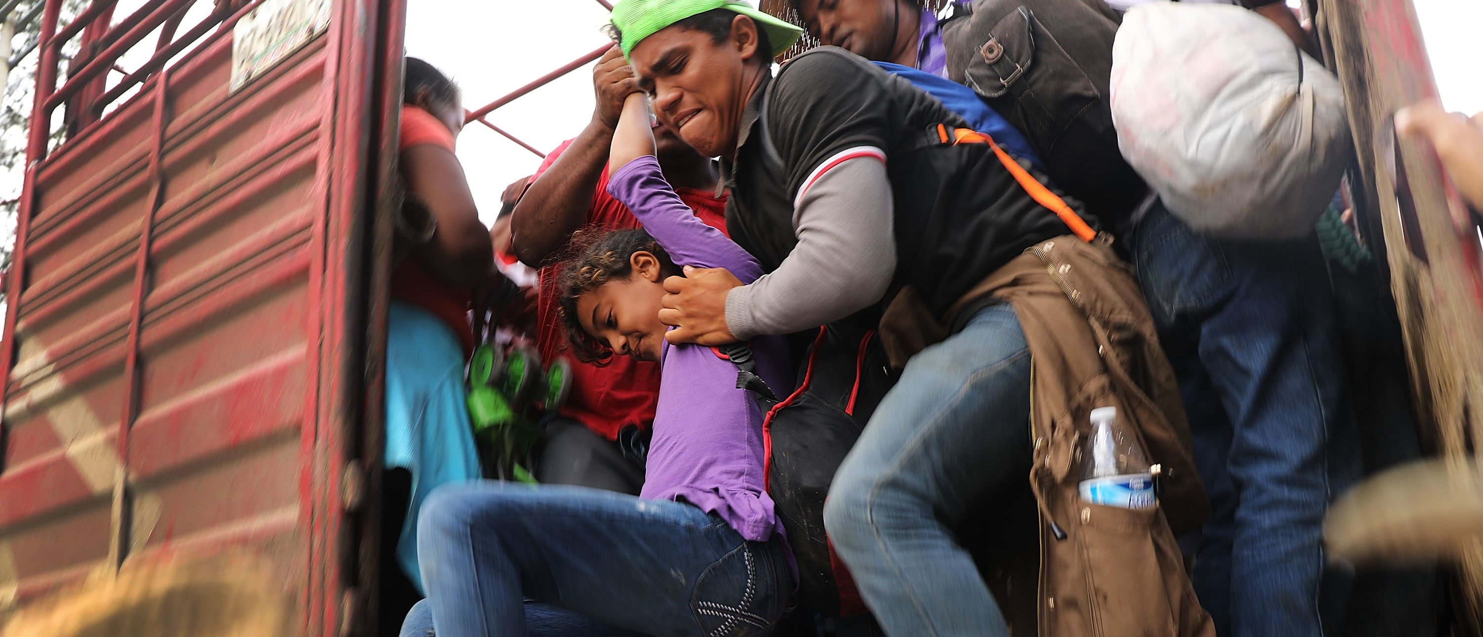 Members of the Central American migrant caravan attempt to get into the back of a truck as they move to the next town on November 02, 2018 in Donaji, Mexico. (Photo by Spencer Platt/Getty Images)
