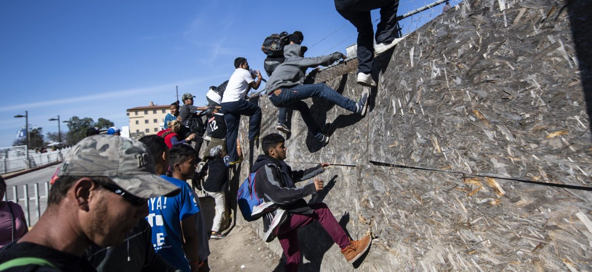 A group of Central American migrants -mostly from Honduras- get over a fence as they try to reach the US-Mexico border near the El Chaparral border crossing in Tijuana, Baja California State, Mexico, on November 25, 2018./ PEDRO PARDO/AFP/Getty Images