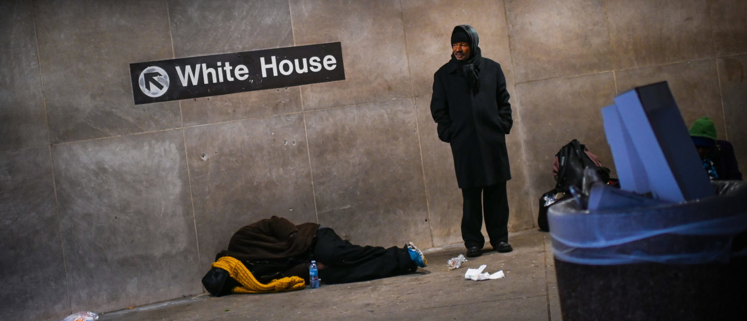 A homeless person sleeps below a sign indicating the exit to the White House at McPherson Square Metro station in Washington, DC, on December 12, 2018. (Photo: ERIC BARADAT/AFP/Getty Images)