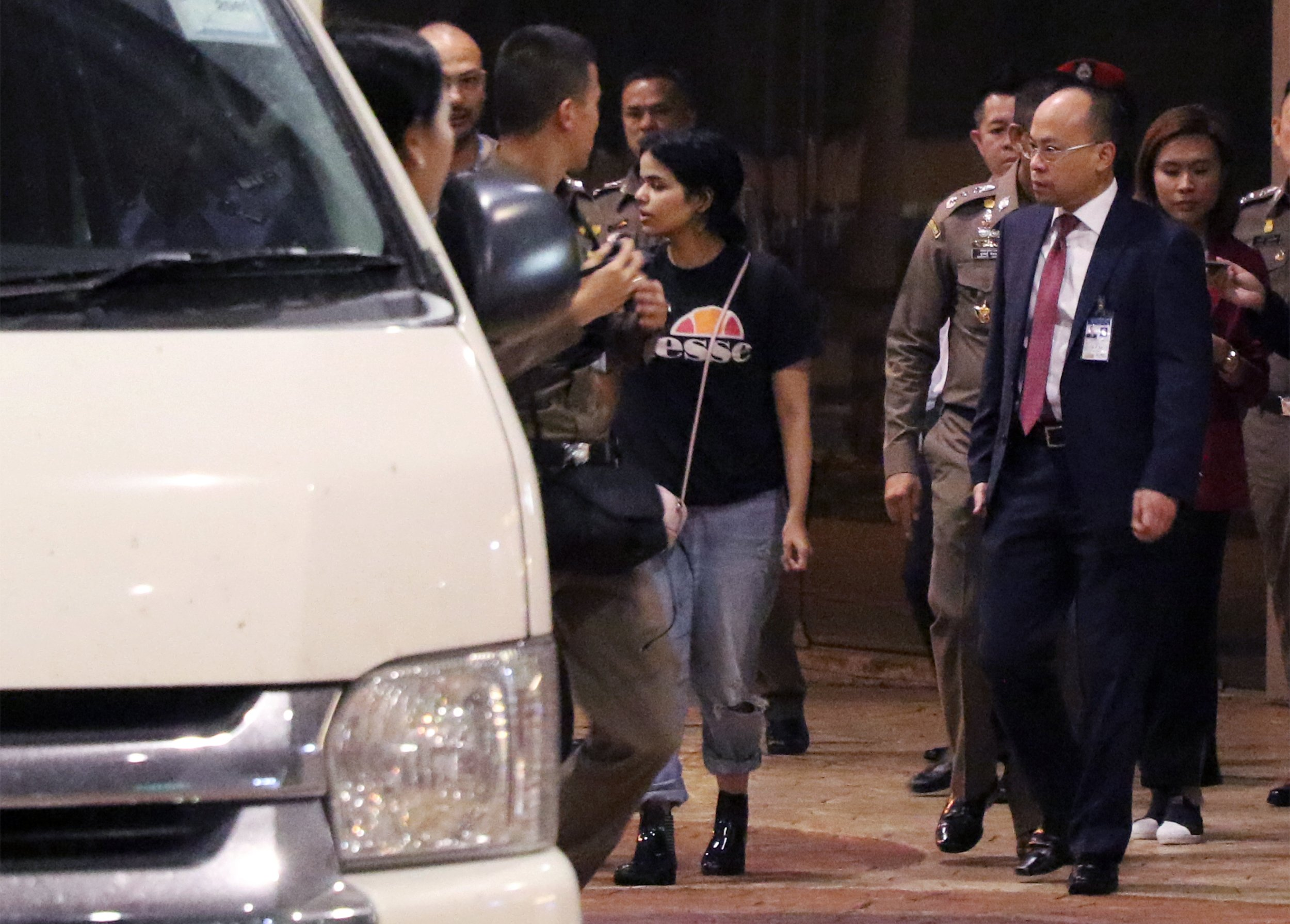 18-year-old Saudi woman Rahaf Mohammed al-Qanun (C) is escorted to a vehicle by the Thai immigration officer and United Nations High Commissioner for Refugees (UNHCR) officials at the Suvarnabhumi international airport in Bangkok on January 7, 2019. (AFP/Getty Images)