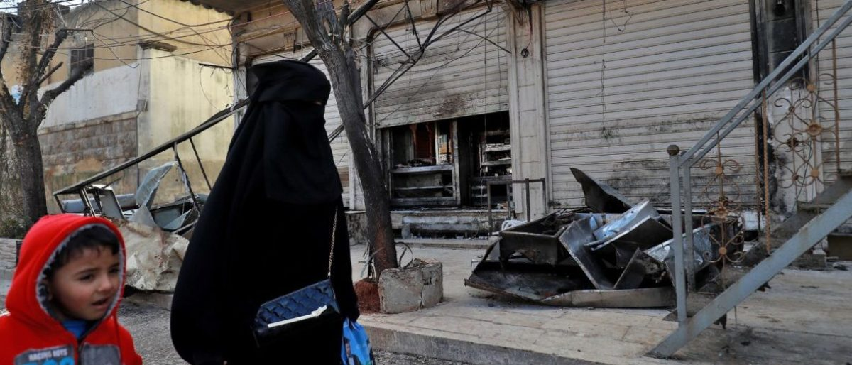 """A Syrian woman and child walk past the shuttered doors of a restaurant which was the site of a suicide attack targeting US-led coalition forces in the flashpoint northern Syrian city of Manbij which killed four US servicemen the previous day on January 17, 2019. - The bombing, claimed by the Islamic State group, comes after US President Donald Trump's shock announcement last month that he was ordering a full troop withdrawal from Syria because the jihadists had been """"largely defeated"""". (Photo by Delil SOULEIMAN / AFP)"""