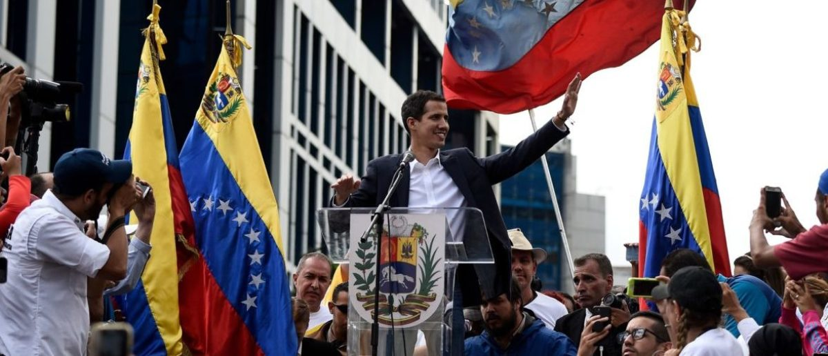 """Venezuela's National Assembly head Juan Guaido (C) waves to the crowd during a mass opposition rally against leader Nicolas Maduro in which he declared himself the country's """"acting president"""", on the anniversary of a 1958 uprising that overthrew military dictatorship, in Caracas on January 23, 2019. - """"I swear to formally assume the national executive powers as acting president of Venezuela to end the usurpation, (install) a transitional government and hold free elections,"""" said Guaido as thousands of supporters cheered. Moments earlier, the loyalist-dominated Supreme Court ordered a criminal investigation of the opposition-controlled legislature. (Photo by Federico PARRA / AFP)"""