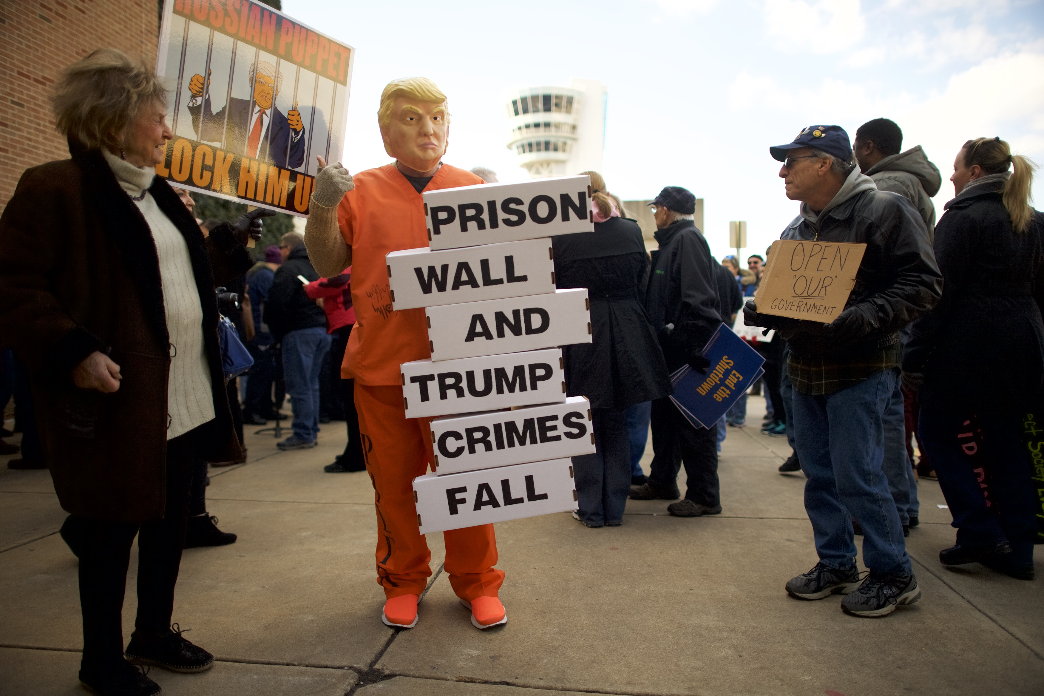 "A protester dressed as President Donald Trump holds a placard stating ""PRISON WALL AND TRUMP CRIMES FALL"" while demonstrating with Philadelphia Airport TSA and airport workers outside the Philadelphia International Airport on January 25, 2019 in Philadelphia, Pennsylvania. (Photo by Mark Makela/Getty Images)"