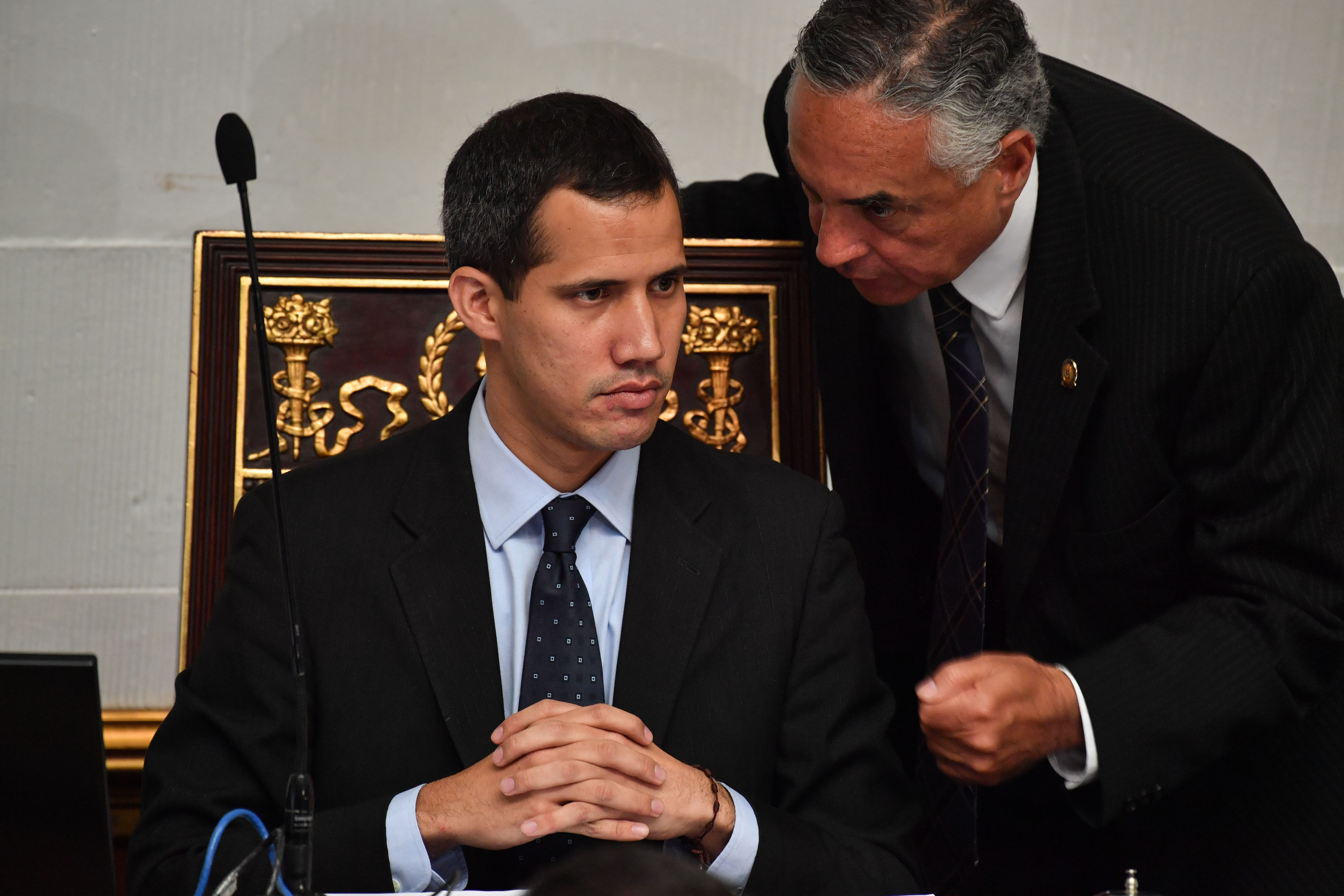 """Venezuela's National Assembly head and self-proclaimed """"acting president"""" Juan Guaido (L), listens to deputy Rafael Veloz, during a session at the National Assembly in Caracas on January 29, 2019. (YURI CORTEZ/AFP/Getty Images)"""