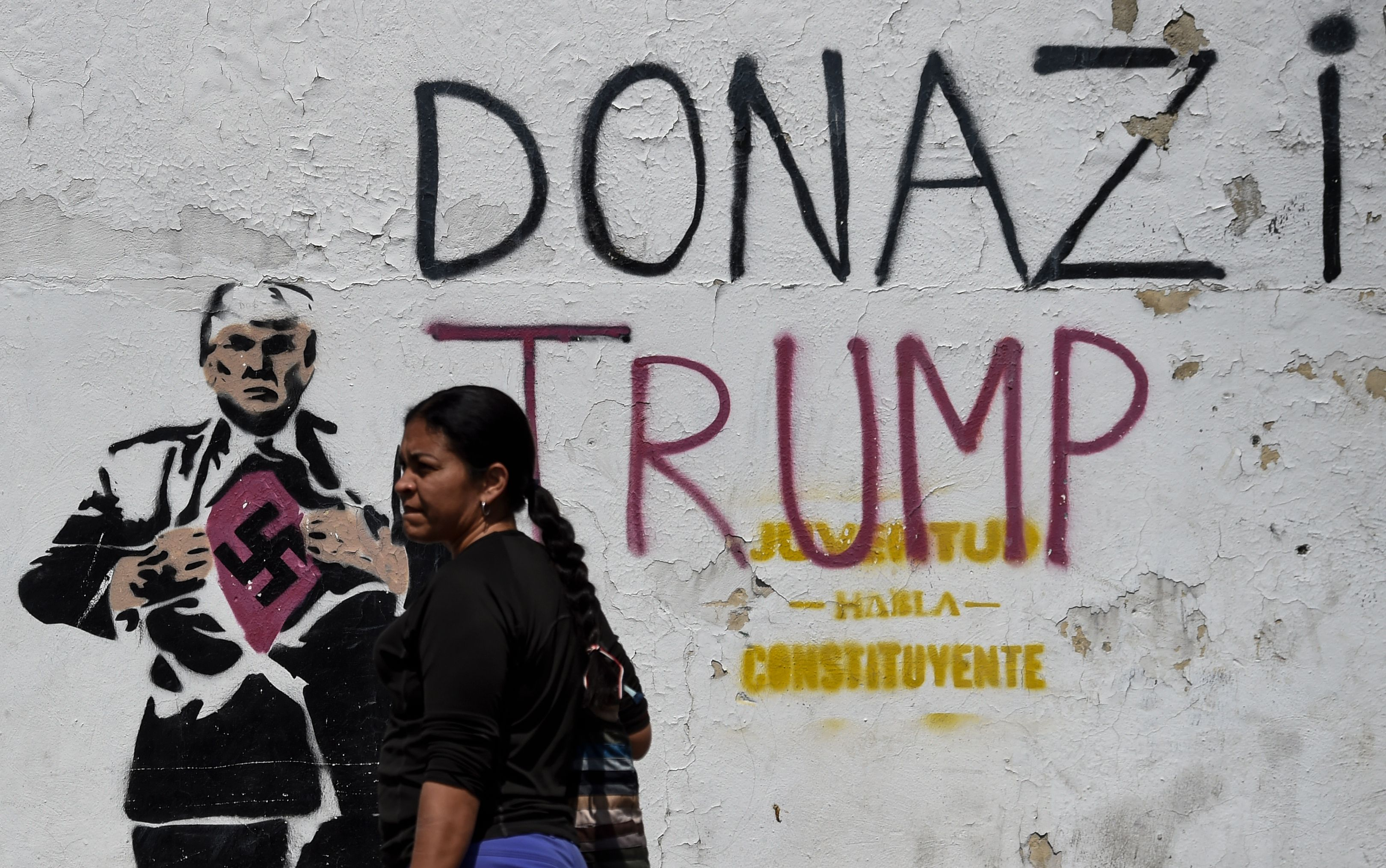 A woman walks past a painting of US President Donald Trump in Caracas on January 29, 2019. (JUAN BARRETO/AFP/Getty Images)