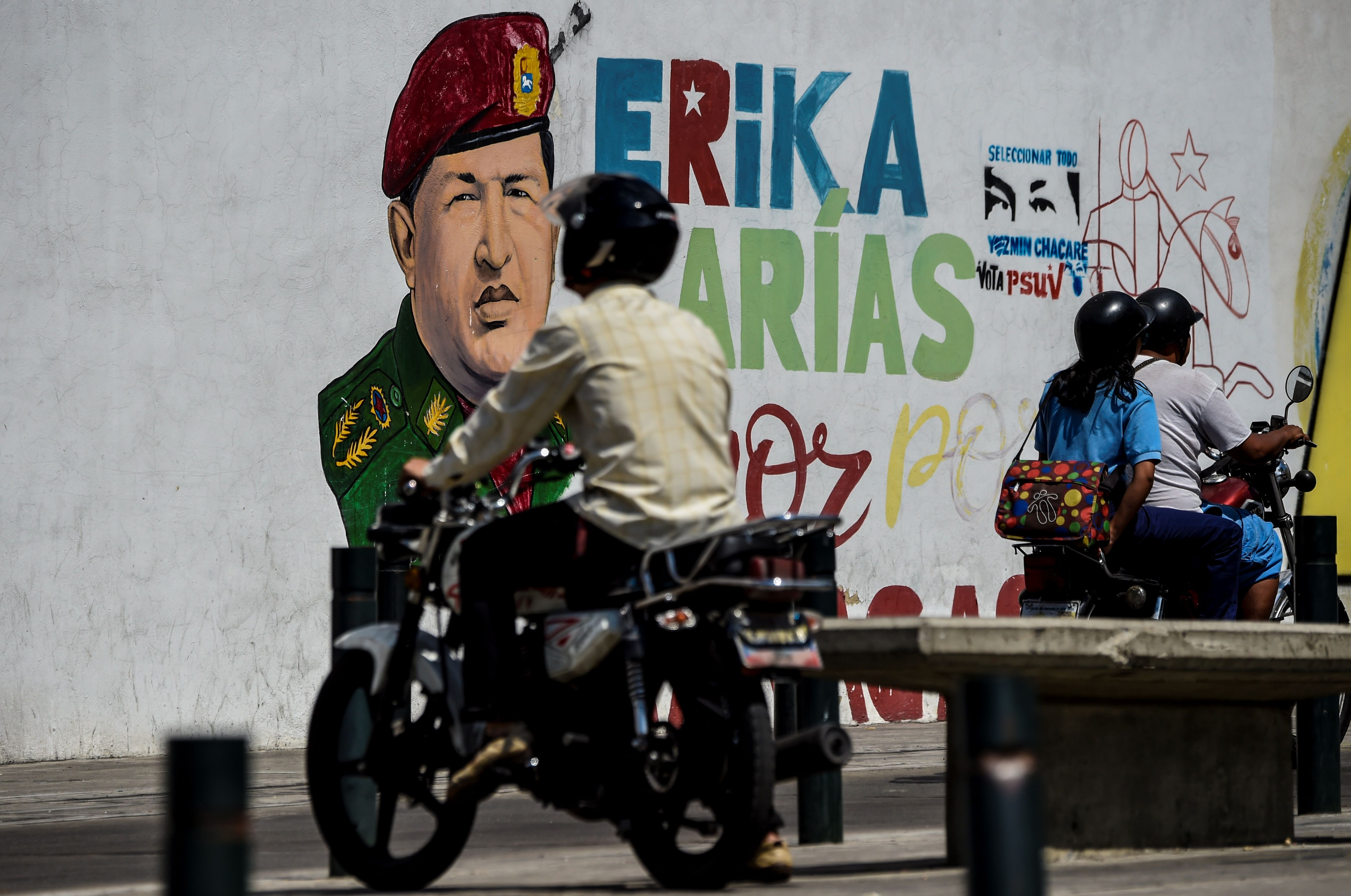 A motorcyclist drives past a painting of late Venezuelan President Hugo Chavez on a wall in Caracas on January 29, 2019. (JUAN BARRETO/AFP/Getty Images)