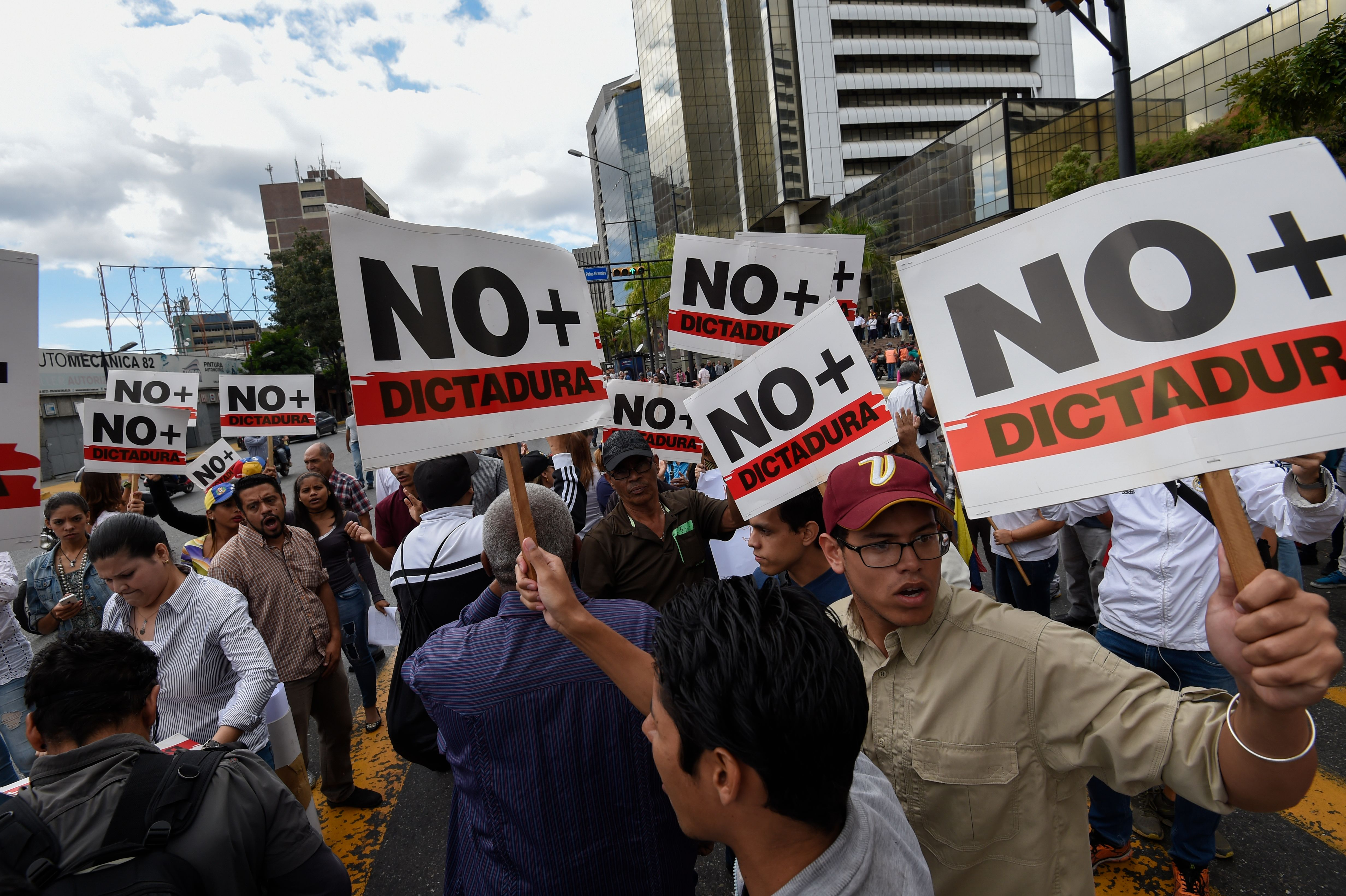 "Opposition demonstrators take part in protest against the government of President Nicolas Maduro, called by opposition leader and self-proclaimed ""acting president"" Juan Guaido, near Parque Cristal, in Caracas on January 30, 2019. - Venezuelan President Nicolas Maduro hit out Wednesday at military ""mercenaries"" he says are conspiring to divide the armed forces and plot a coup as the opposition planned a new protest to force the socialist leader from power. (Photo by JUAN BARRETO / AFP)"