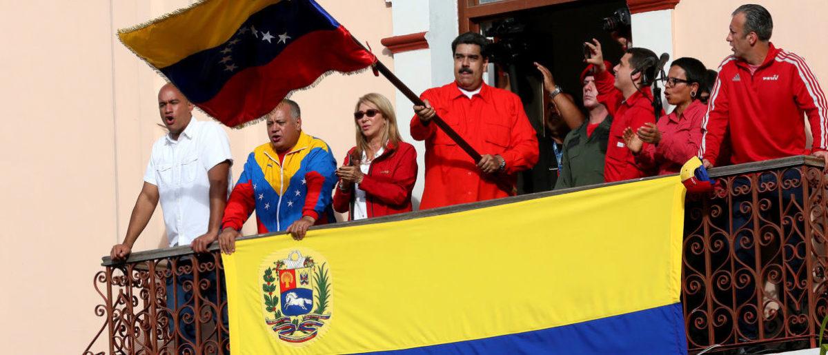 President of Venezuela Nicolás Maduro (C) waves a national flag. (Edilzon Gamez/Getty Images)