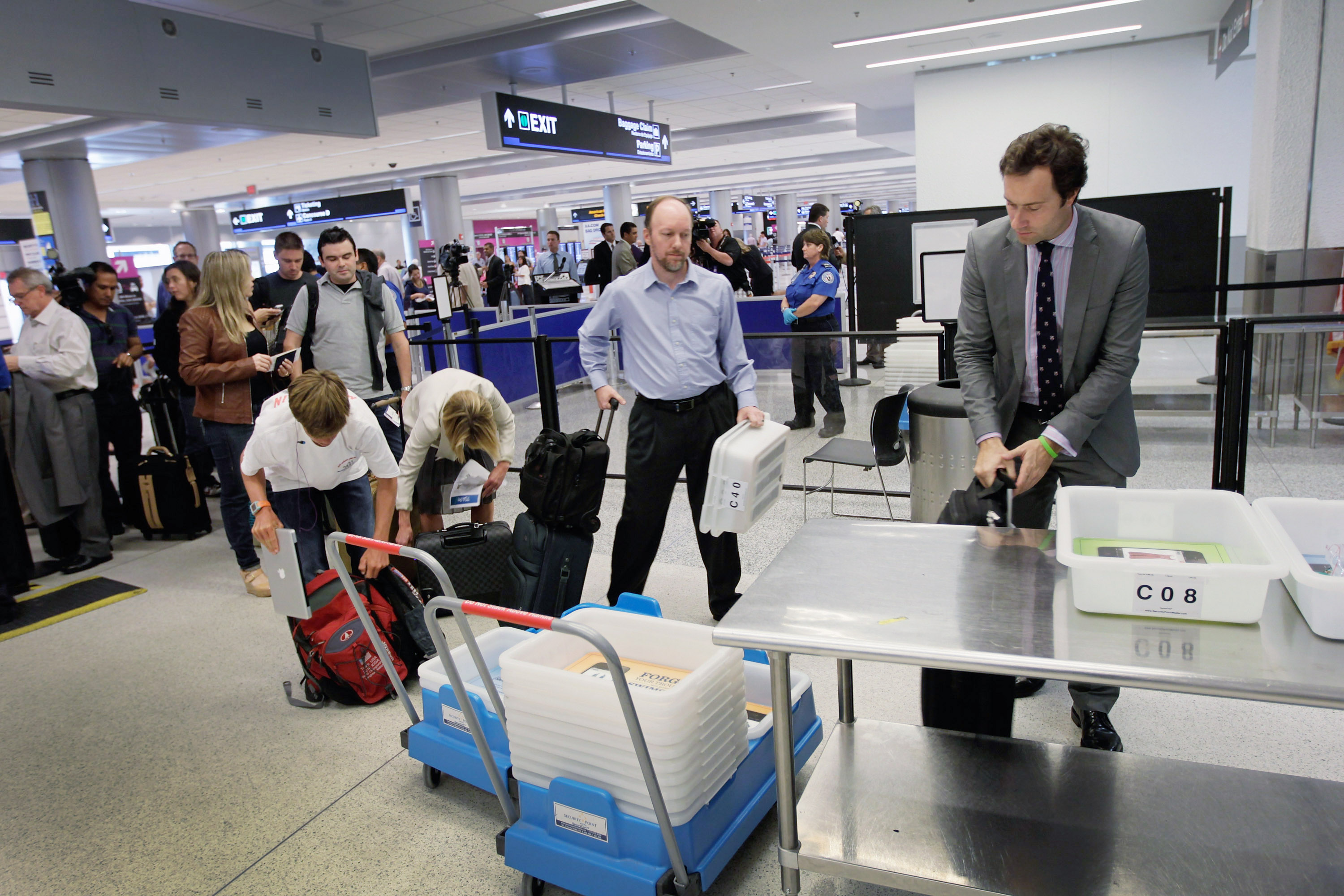 Passengers wait to clear security next to the newly opened TSA PreCheck lane which the Transportation Security Administration launched to cut down the time prescreened passengers need to stand in the traditional security line at Miami International Airport on October 4, 2011 in Miami, Florida. (Photo by Joe Raedle/Getty Images)