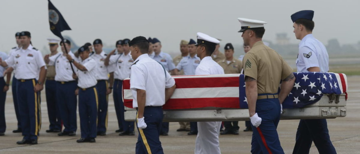 US soldiers carry a US flag draped casket containing what is believed to be remains of a US service man listed as missing in action during the Vietnam war towards a US Airforce aircraft at a MIA (missing in action) repatriation ceremony held at Hanoi's Noi Bai airport on November 30, 2012. The three remains which were repatriated at this 125th post-war repatriation of US remains from Vietnam were recovered by recent joint MIA research conducted by Vietnamese and US field teams. To date 985 US soldiers from the Vietnam War have been identified since 1973 - 689 from Vietnam, 258 from Laos, 35 from Cambodia and 3 from China, according to a press release from the US embassy in Hanoi. Some 1,661 US soldiers are still unaccounted for from the war, including 1,282 in Vietnam, according to the press release. AFP PHOTO / HOANG DINH Nam