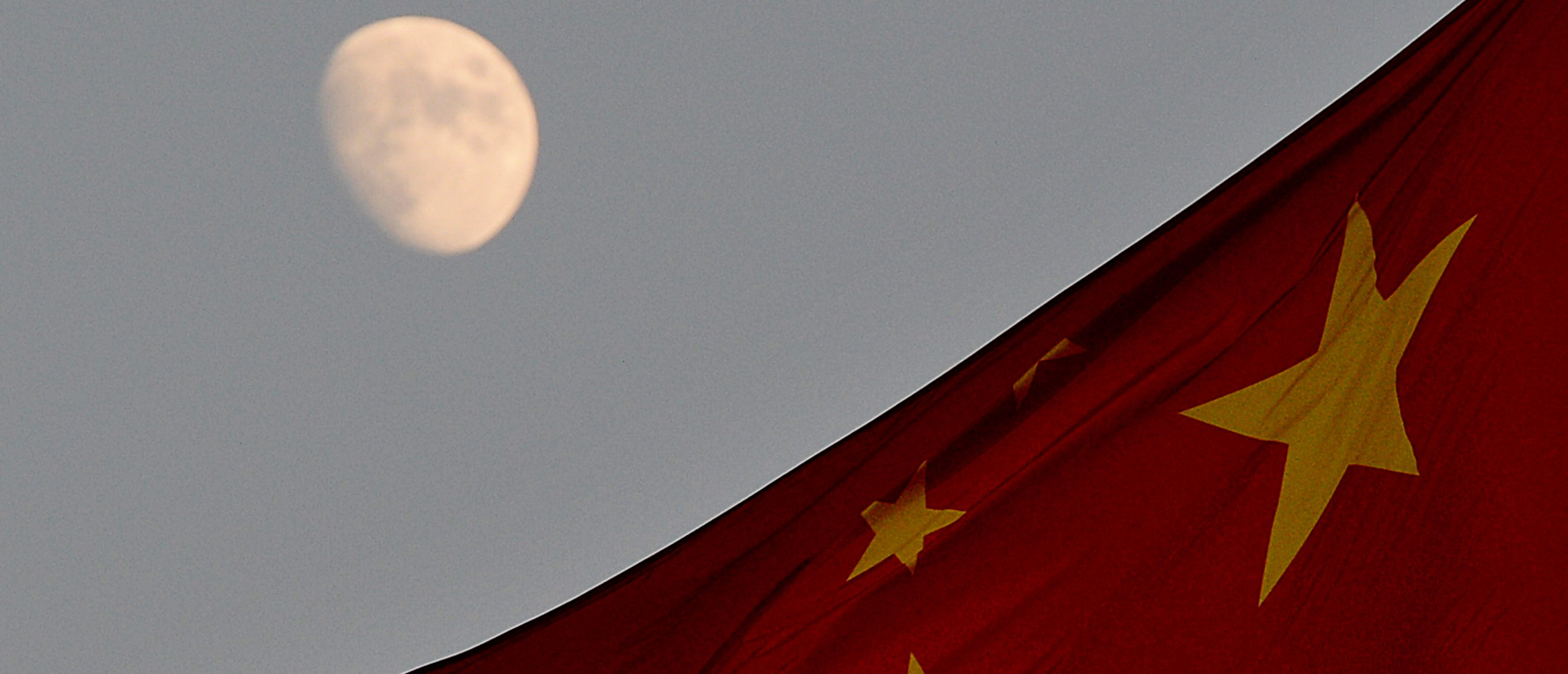 The Chinese flag is seen in front of a view of the moon at Tiananmen Square in Beijing on December 13, 2013. (Photo credit should read MARK RALSTON/AFP/Getty Images)