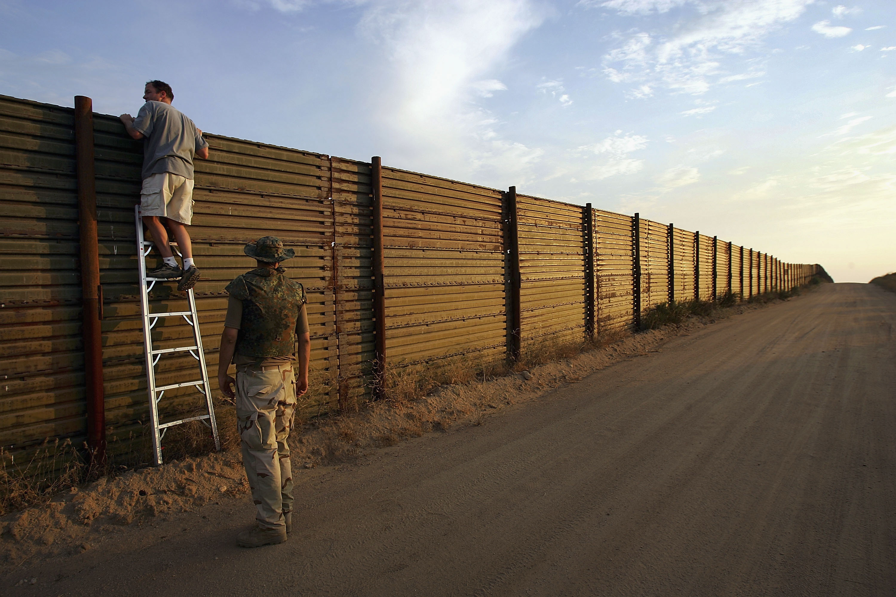 CAMPO, CA - JULY 19: Volunteers look over the US-Mexico border fence to see how illegal border crossers may jump the fence before going on the nightly patrol by citizen volunteers searching for people crossing into the US illegally from Mexico on July 19, 2005 near Campo, California in eastern San Diego County. (Photo by David McNew/Getty Images)