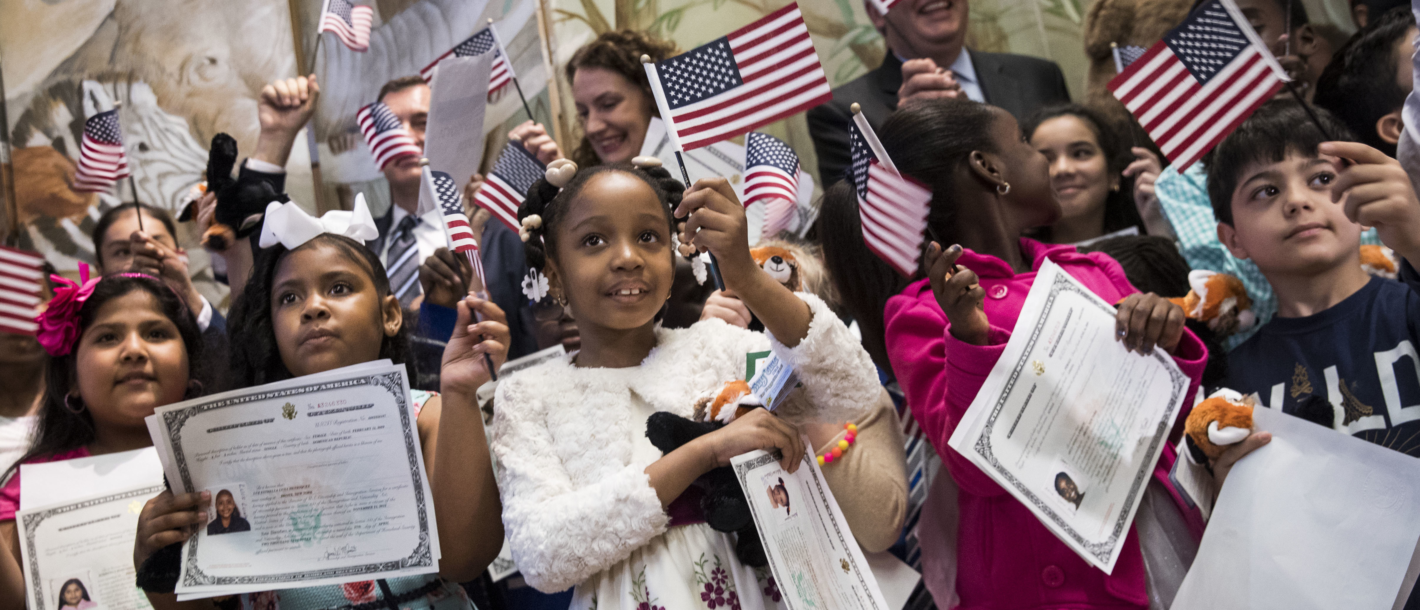 Children wave American flags and hold their certificates of citizenship after becoming U.S. citizens during a citizenship ceremony at The Bronx Zoo, May 5, 2017 in The Bronx borough of New York City. (Photo by Drew Angerer/Getty Images)