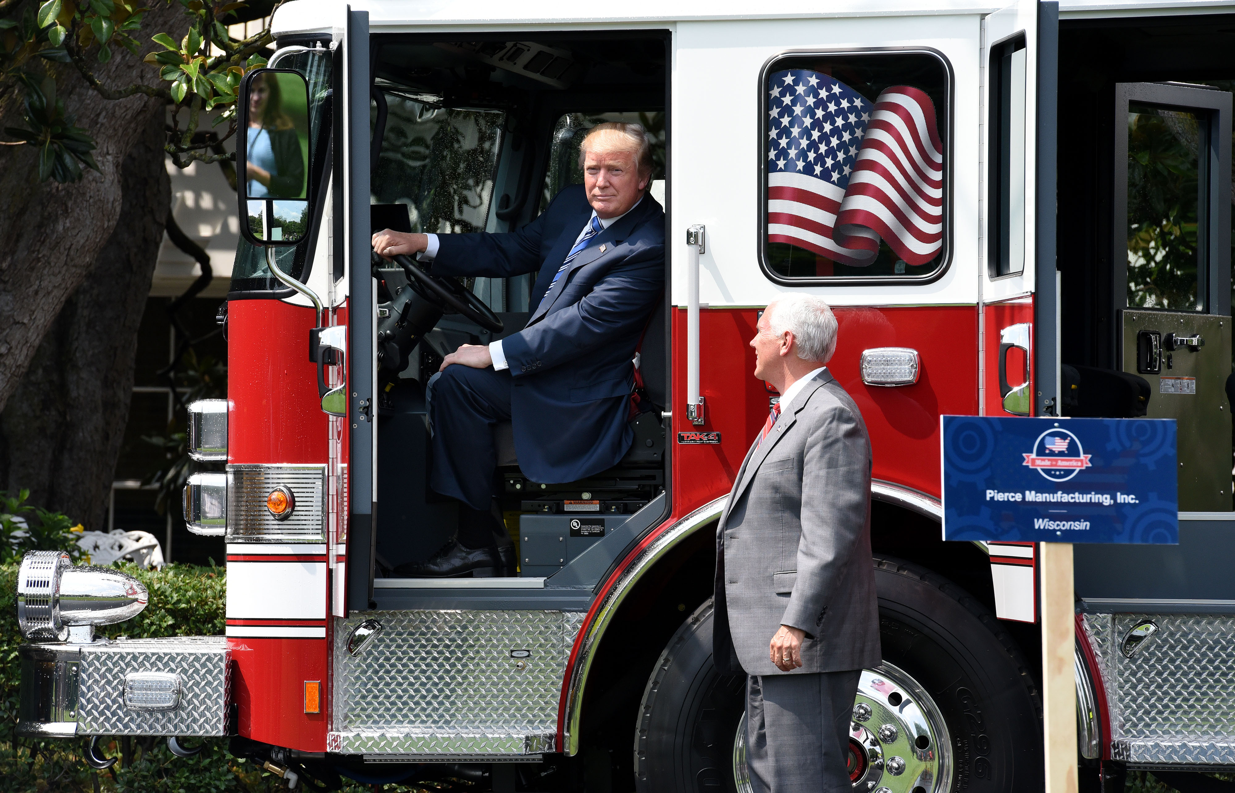 "President Donald Trump examines a fire truck from Wisconsin-based manufacturer Pierce as Vice President Mike Pence looks on during a ""Made in America"" product showcase event on the South Lawn at the White House in Washington, DC, on July 17, 2017. / AFP PHOTO / Olivier Douliery (Photo credit should read OLIVIER DOULIERY/AFP/Getty Images)"