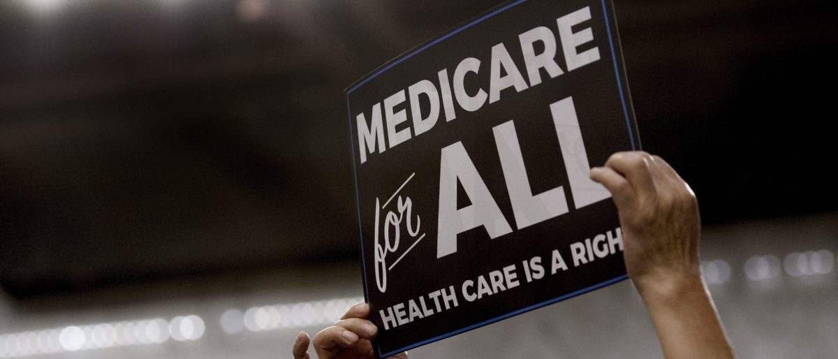 A member of the audience holds up a placard as US Senator Bernie Sanders, Independent from Vermont, discusses Medicare for All/ AFP PHOTO / JIM WATSON/ Getty Images