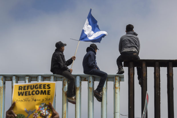 TIJUANA, MEXICO - APRIL 29: People hold a Honduran flag and look into the United States from atop a section of border fence as members of a caravan of Central American asylum seekers arrive to a rally on April 29, 2018 in Tijuana, Baja California Norte, Mexico. More than 300 immigrants, the remnants of a caravan of Central Americans that journeyed across Mexico to ask for asylum in the United States, have reached the border to apply for legal entry. (Photo by David McNew/Getty Images)