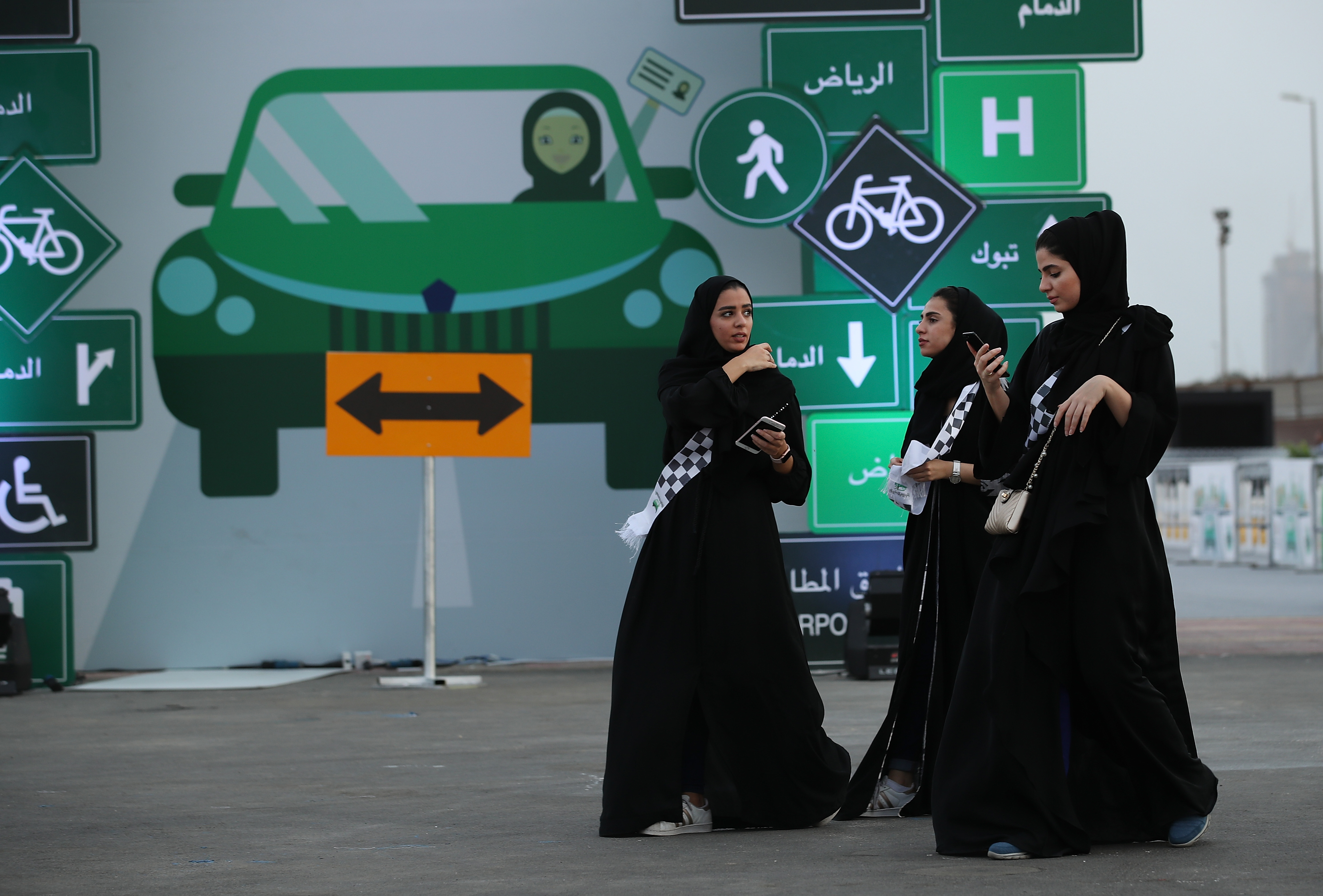 JEDDAH, SAUDI ARABIA - JUNE 21: Young women wearing the traditional abaya walk past a sign as they help to organize an outdoor educational driving event for women on June 21, 2018 in Jeddah, Saudi Arabia. Saudi Arabia is scheduled to lift its ban on women driving, which has been in place since 1957, on June 24. The Saudi government, under Crown Prince Mohammad Bin Salman, is phasing in an ongoing series of reforms to both diversify the Saudi economy and to liberalize its society. The reforms also seek to empower women by restoring them basic legal rights, allowing them increasing independence and encouraging their participation in the workforce. Saudi Arabia is among the most conservative countries in the world and women have traditionally had much fewer rights than men. (Photo by Sean Gallup/Getty Images)