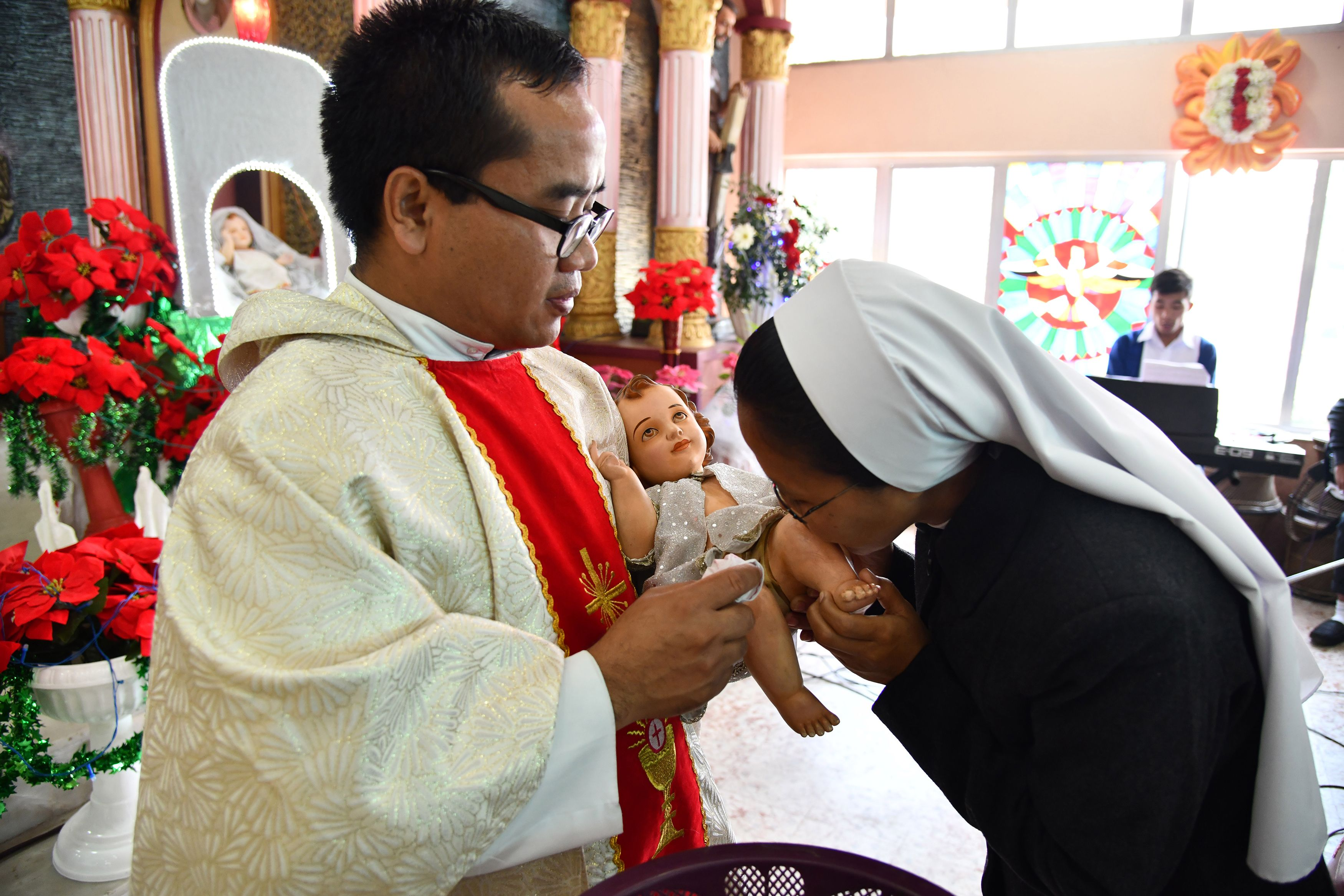 An Indian nun kisses a doll depicting the infant Jesus after Christmas prayers at St John's Church in Guwahati on December 25, 2018. (BIJU BORO/AFP/Getty Images)