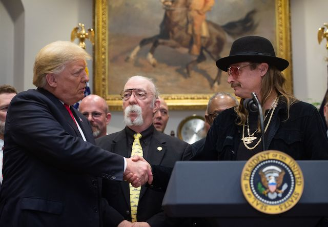 US President Donald Trump shakes hands with musician Kid Rock (R) after signing the Hatch-Goodlatte Music Modernization Act, a bipartisan bill aimed at ensuring artists who released records prior to 1972 are paid royalties from digital services, in the Roosevelt Room of the White House in Washington, DC, October 11, 2018. (Photo credit: LOEB/AFP/Getty Images)