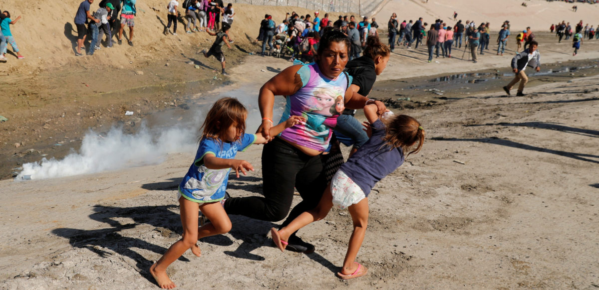 A migrant family, part of a caravan of thousands traveling from Central America en route to the United States, run away from tear gas in front of the border wall between the U.S and Mexico in Tijuana, Mexico, November 25, 2018. REUTERS/Kim Kyung-Hoon