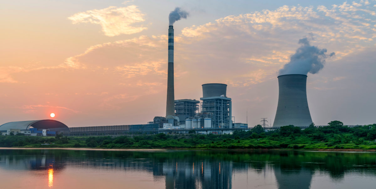 Nuclear power plant after sunset, evening landscape with big chimney, cooling tower at the top of original power plant. Shutterstock