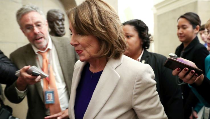 U.S. House Speaker Nancy Pelosi is trailed by reporters as she returns from meetings at the White