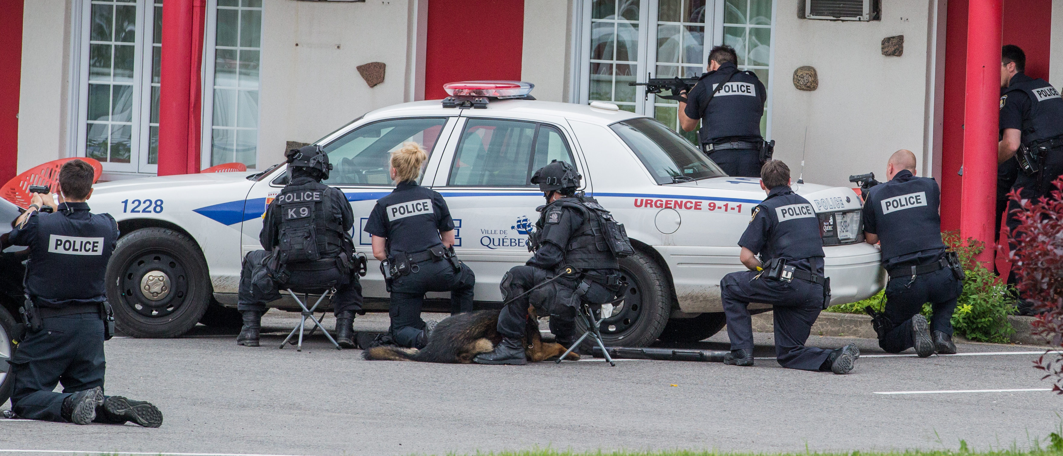Police take cover behind a car during a hostage situation (Shutterstock/Steve Jolicoeur)