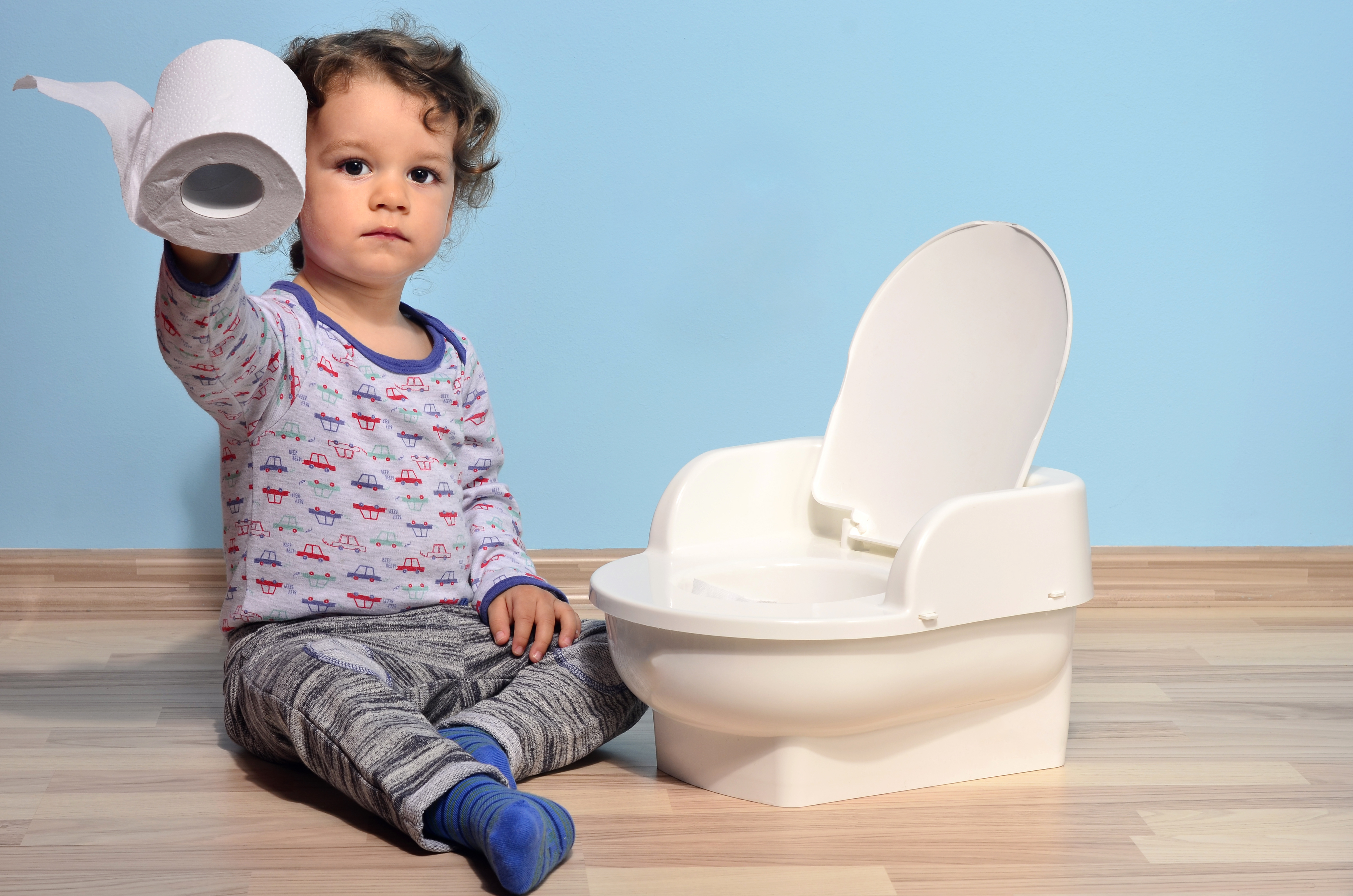 Pictured is a child holding toilet paper next to a mini toilet. SHUTTERSTOCK/ Iulian Valentin